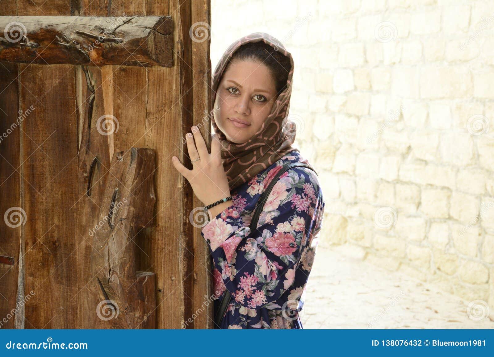 一名年轻回教妇女的画象在木门后的