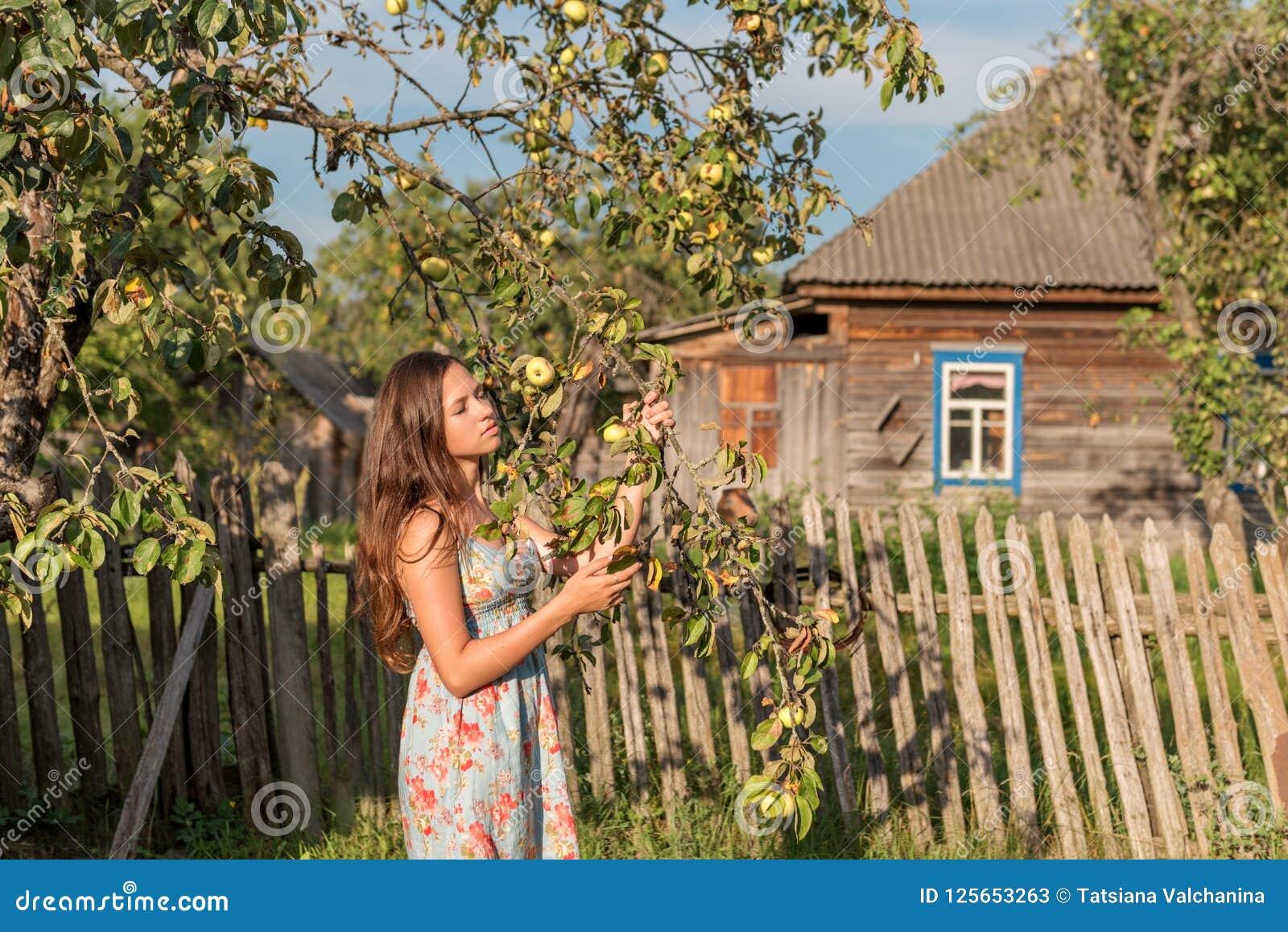 一名年轻少女妇女在一个老村庄房子前面的庭院篱芭附近站立并且闭上她的在早晨的光芒的眼睛