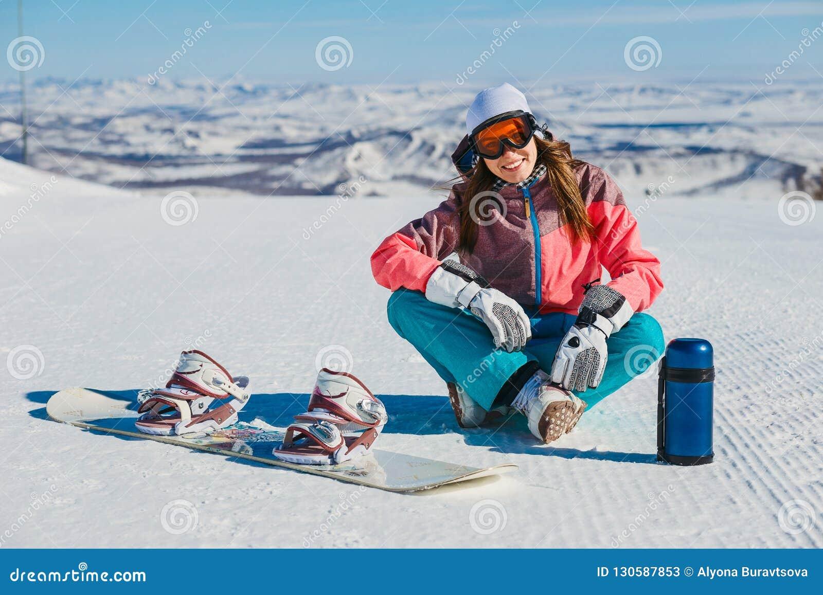一名年轻微笑的妇女坐与雪板和热水瓶的一个山坡