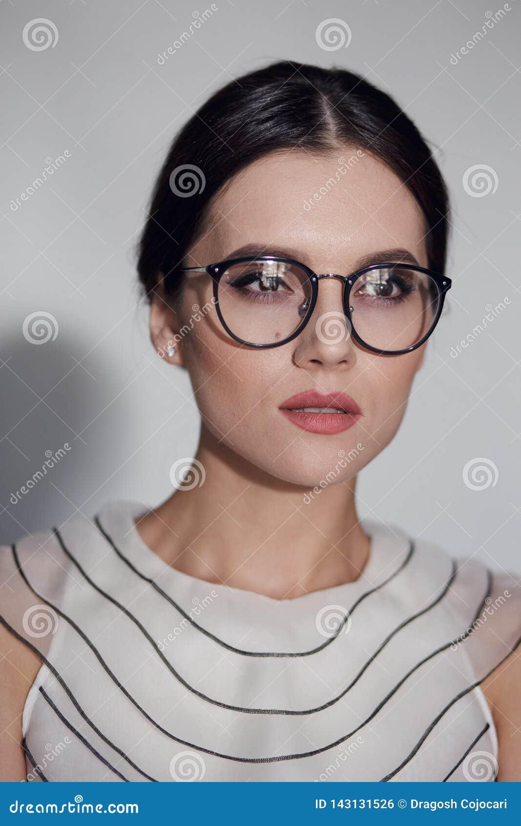 一名年轻端庄的妇女的秀丽画象镜片的,隔绝在白色背景 垂直的视图