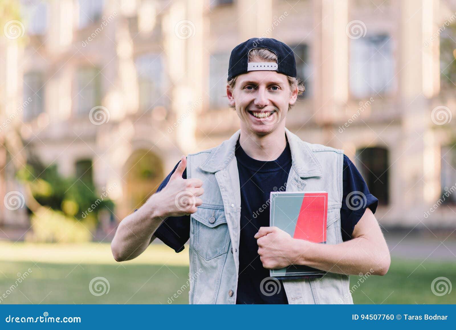 一名微笑的时髦的学生显示在学院校园的背景的赞许