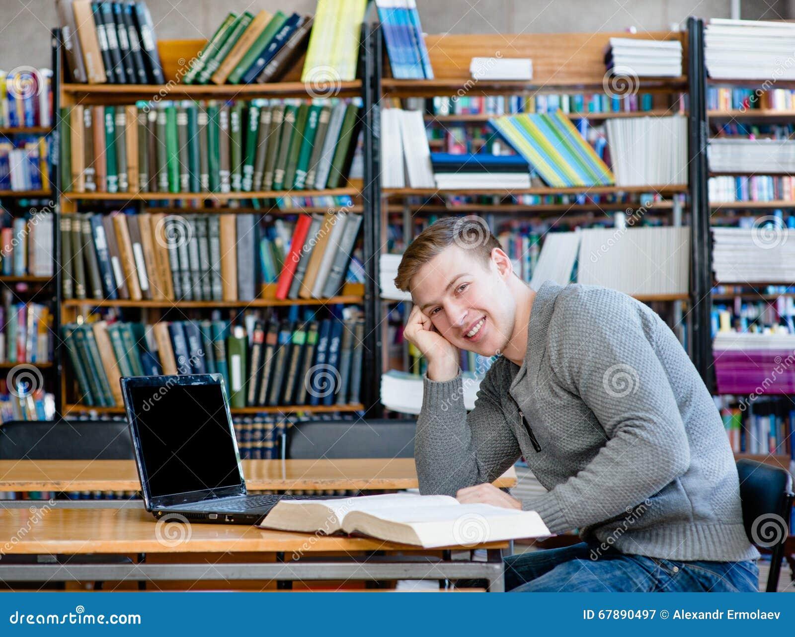 一名愉快的学生的画象有膝上型计算机的在大学图书馆里