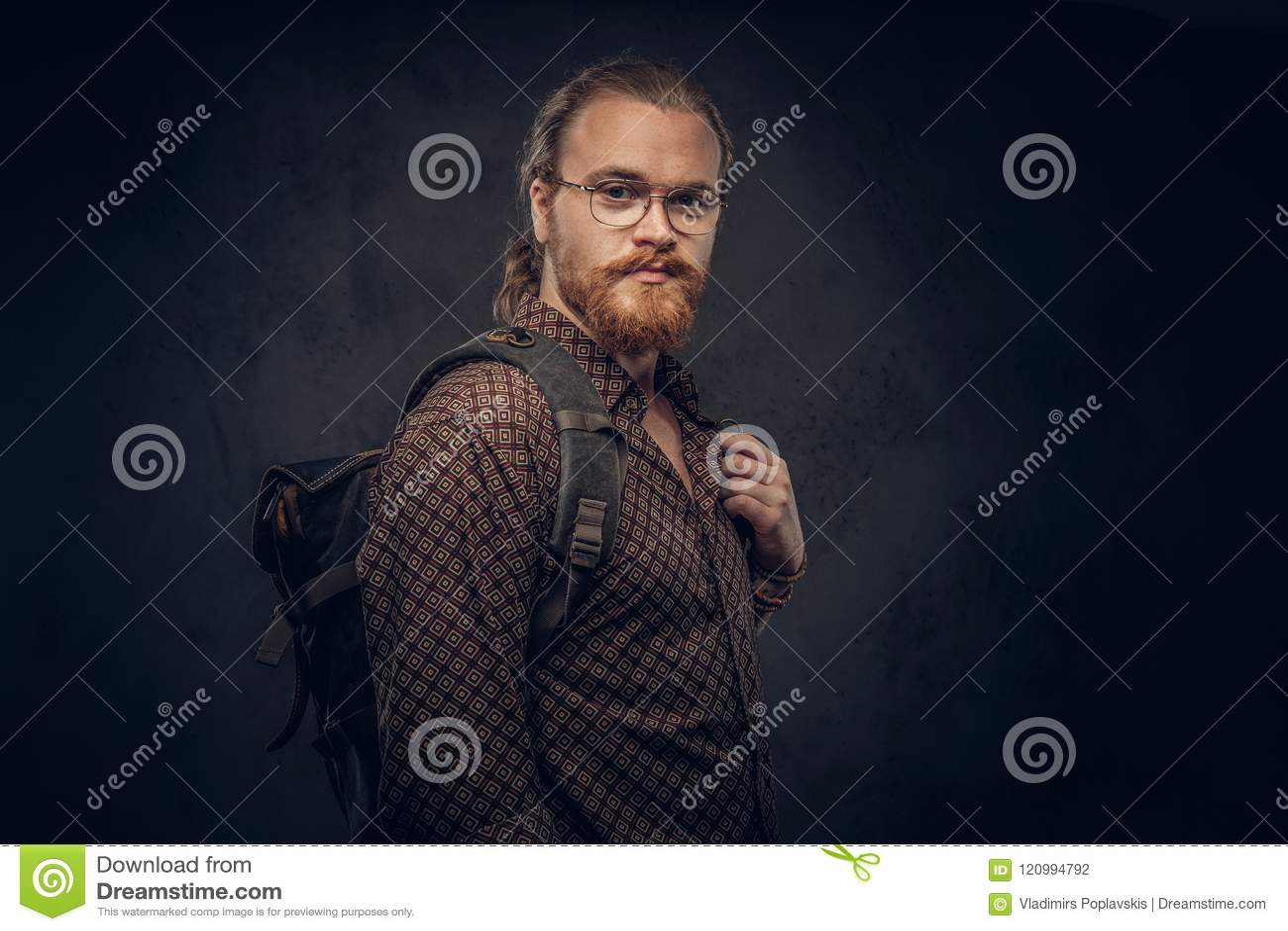 一名红头发人行家学生的画象在一件棕色衬衣穿戴的玻璃的,举行背包,摆在演播室