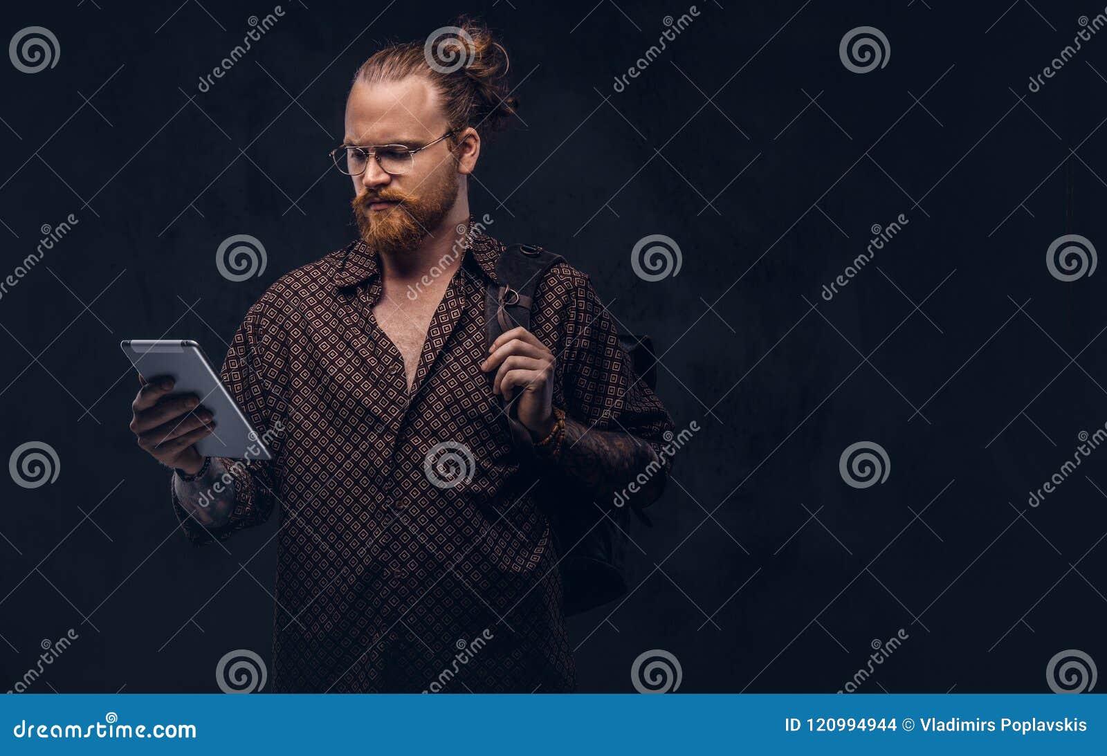一名红头发人行家学生的画象在一种棕色衬衣、举行背包和数字式片剂穿戴的玻璃的,摆在