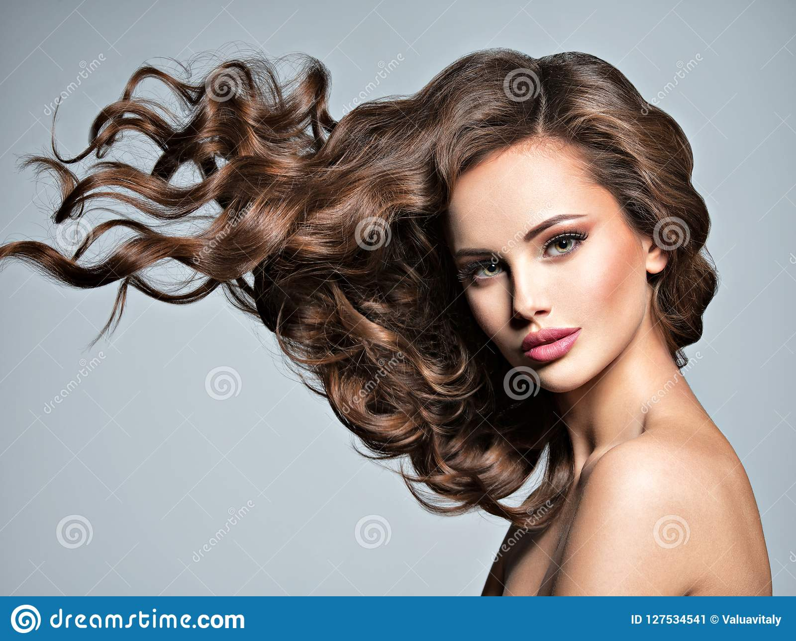 一名美丽的妇女的面孔有长的飞行头发的