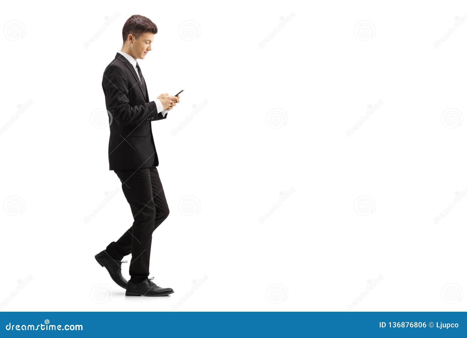 一套黑衣服的年轻人走和键入在一个手机上的