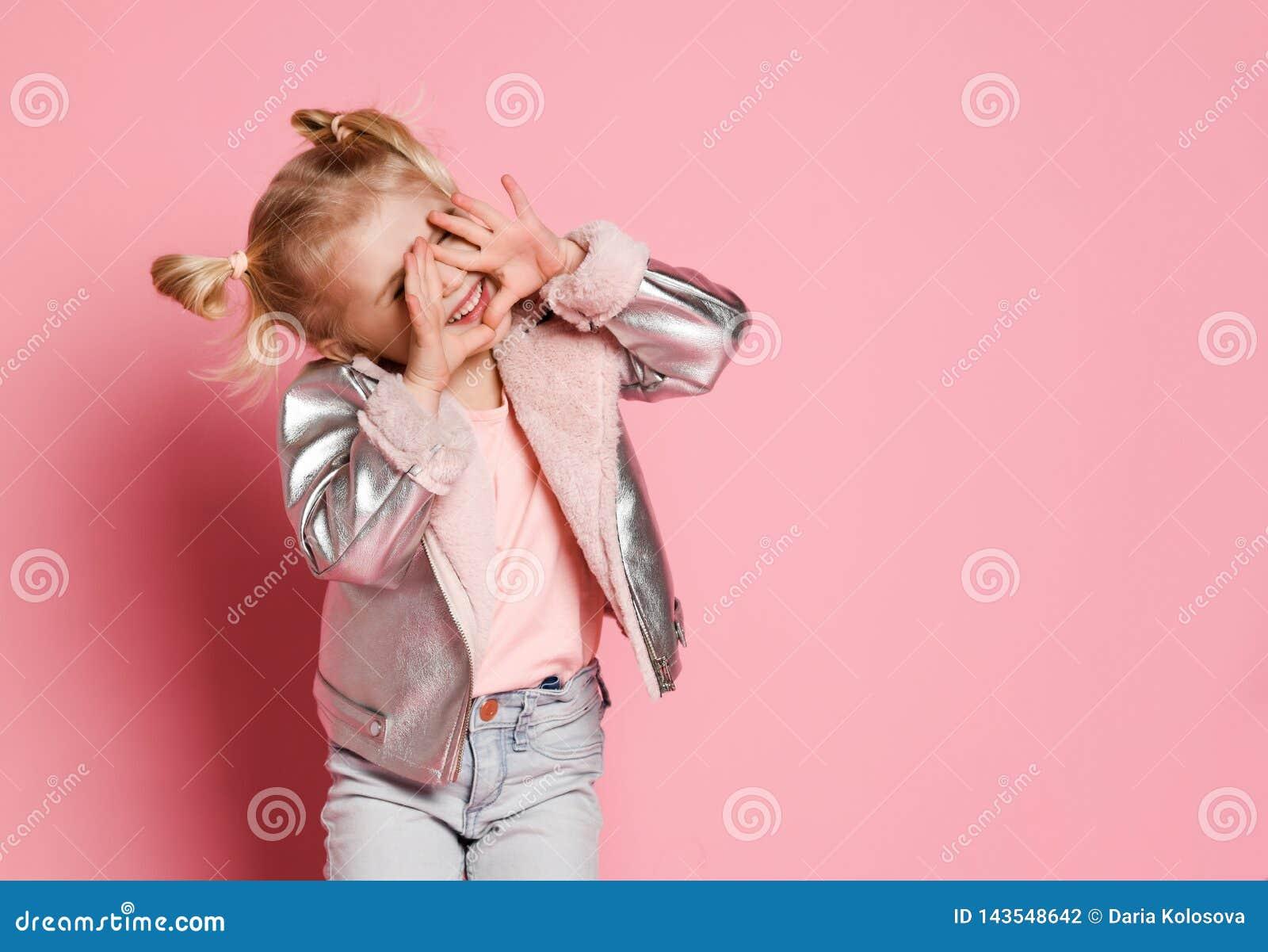 一女孩的画象夸大时髦的衣物的坐桃红色背景和