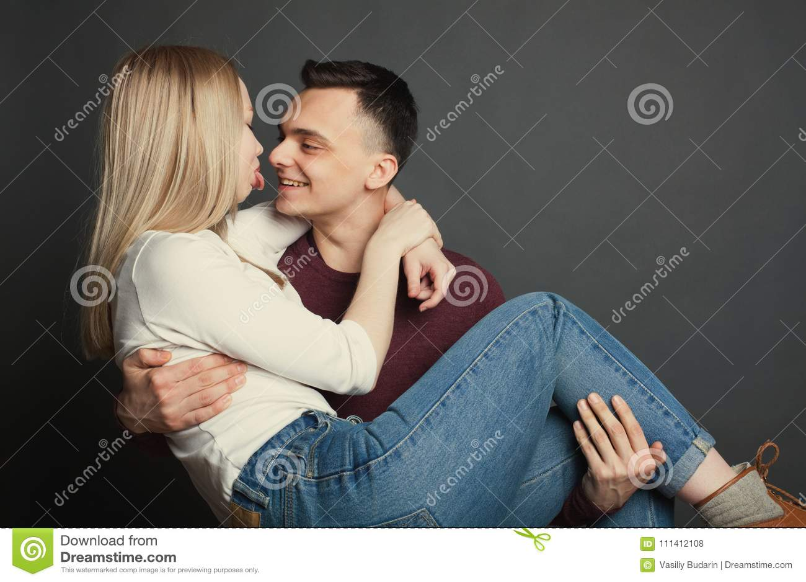 一对美好的年轻夫妇的画象在摆在黑暗的背景的演播室的爱的 人对他的负心爱在他的胳膊和smil