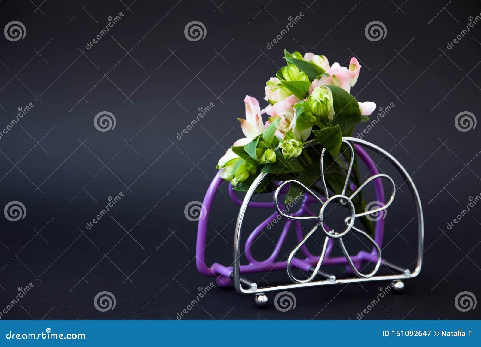 一小花束,在黑背景的一个淡紫色餐巾立场