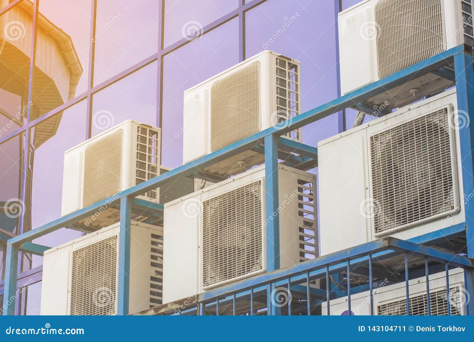 一座大办公楼的墙壁与蓝色窗口和空调的