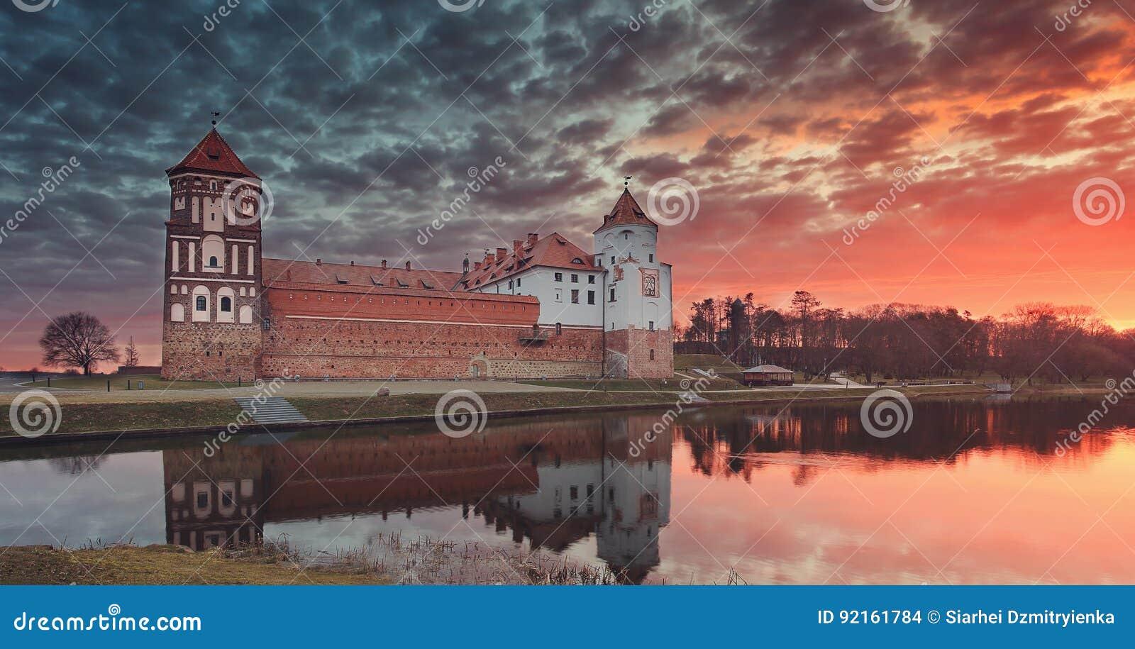 一座老Mirsky城堡的风景反对五颜六色的天空的在美好的黎明