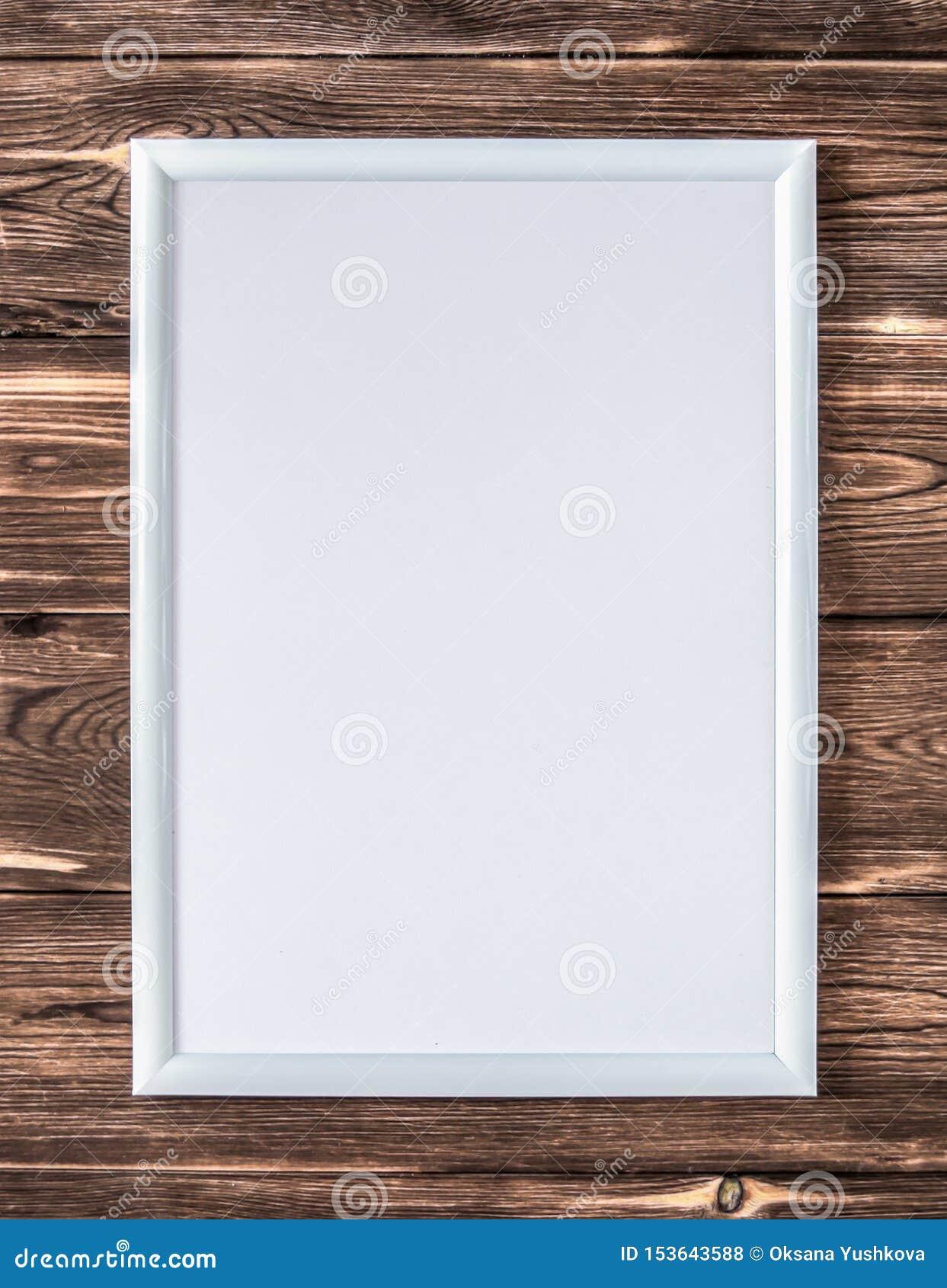 一张图片的空的白色框架在木棕色背景