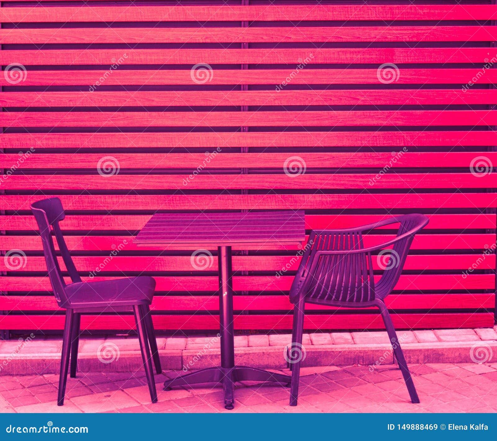 一张桌和两把椅子从木板在街道上站立在城市s咖啡馆在夏天