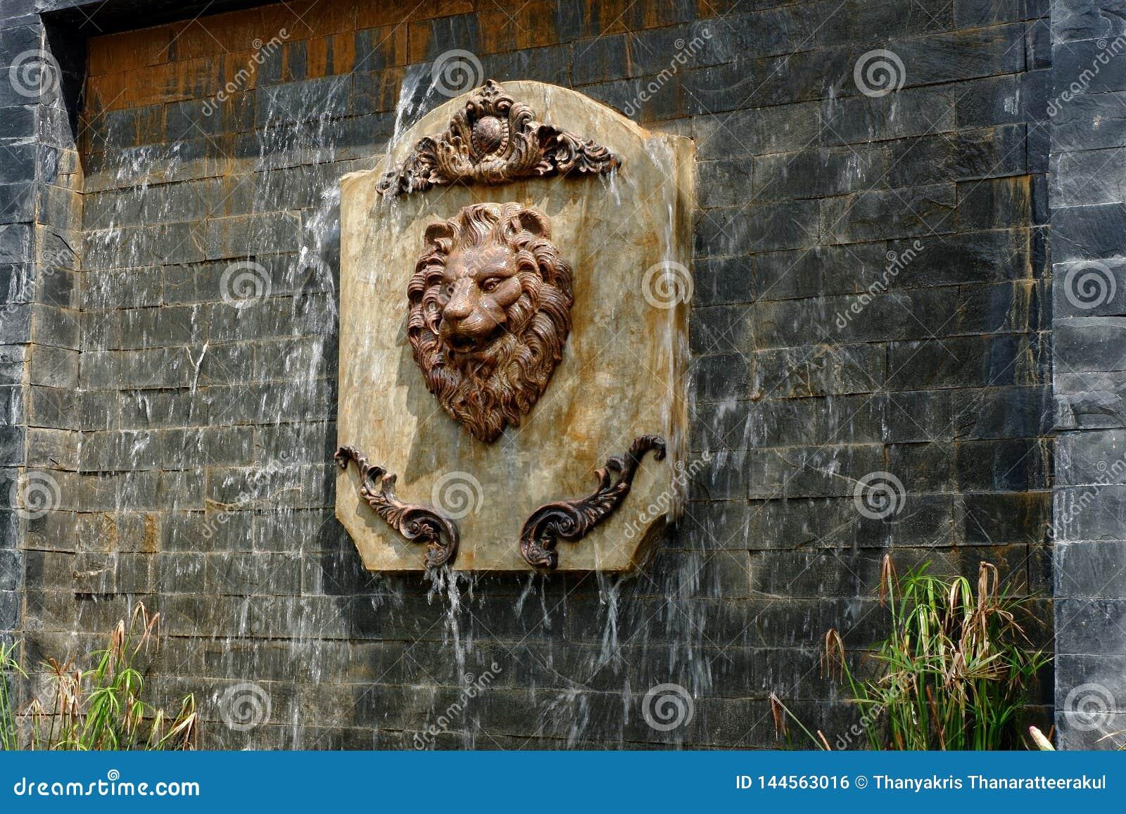 一张狮子面孔的雕象在复制品瀑布的