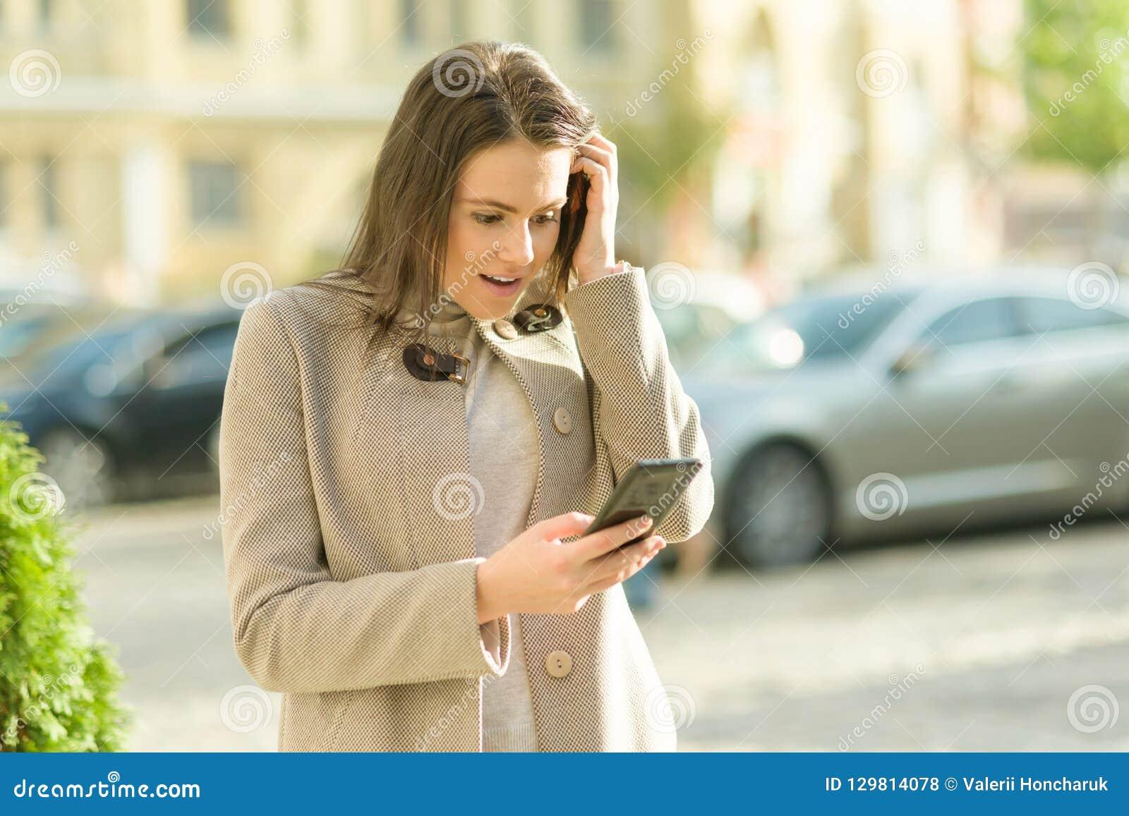 一微笑的愉快的年轻女人的室外画象有智能手机的,城市街道背景,秋天好日子 女孩情感地起反应