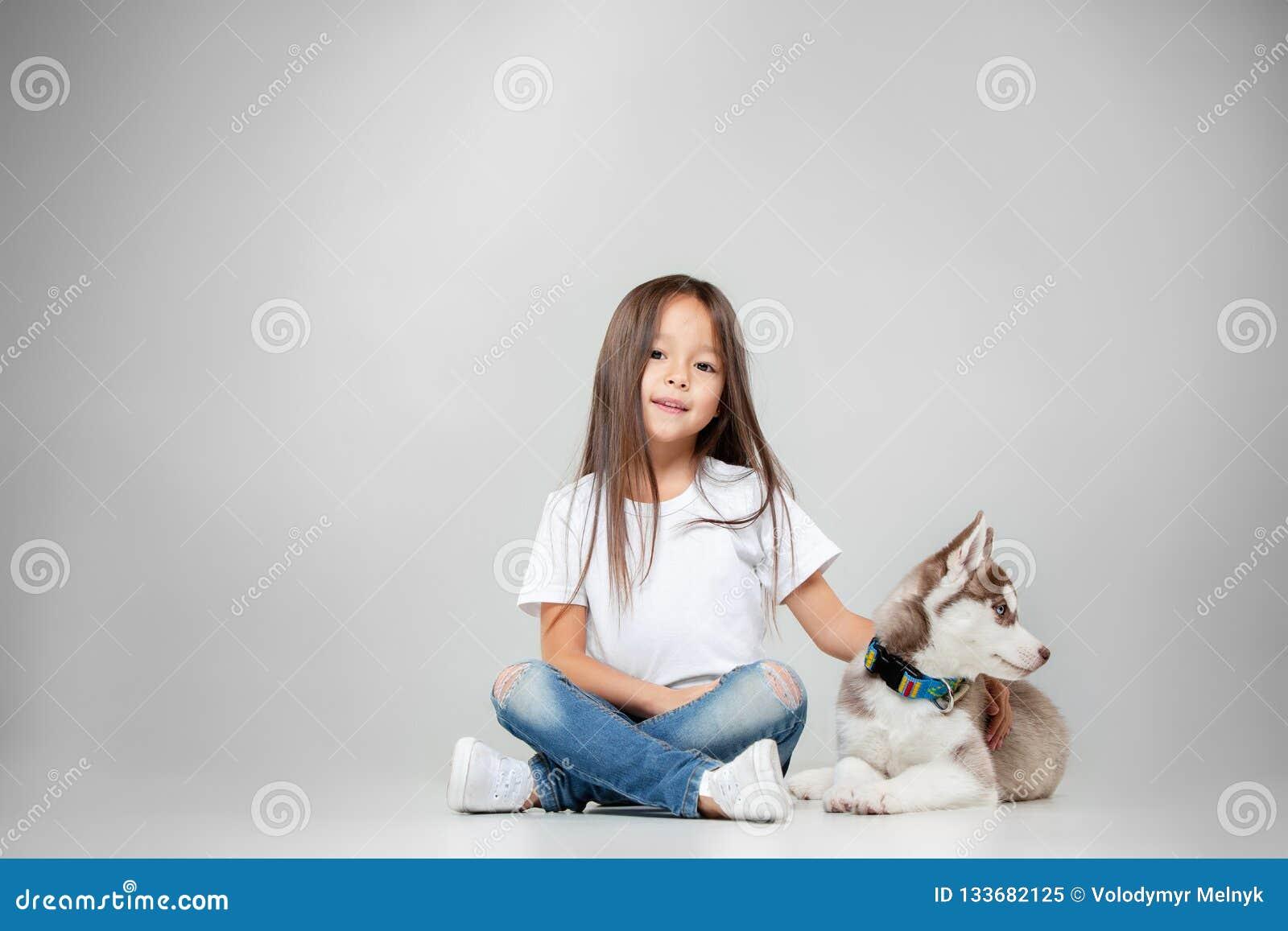 一快乐的女孩的画象获得与西伯利亚爱斯基摩人小狗的乐趣在地板上在演播室