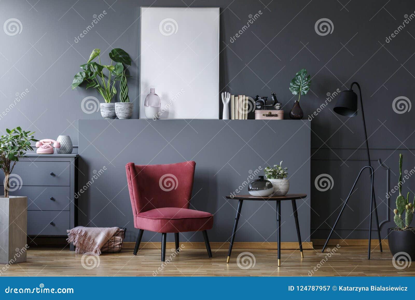 一把红色扶手椅子的真正的照片在黑暗的客厅内部的与