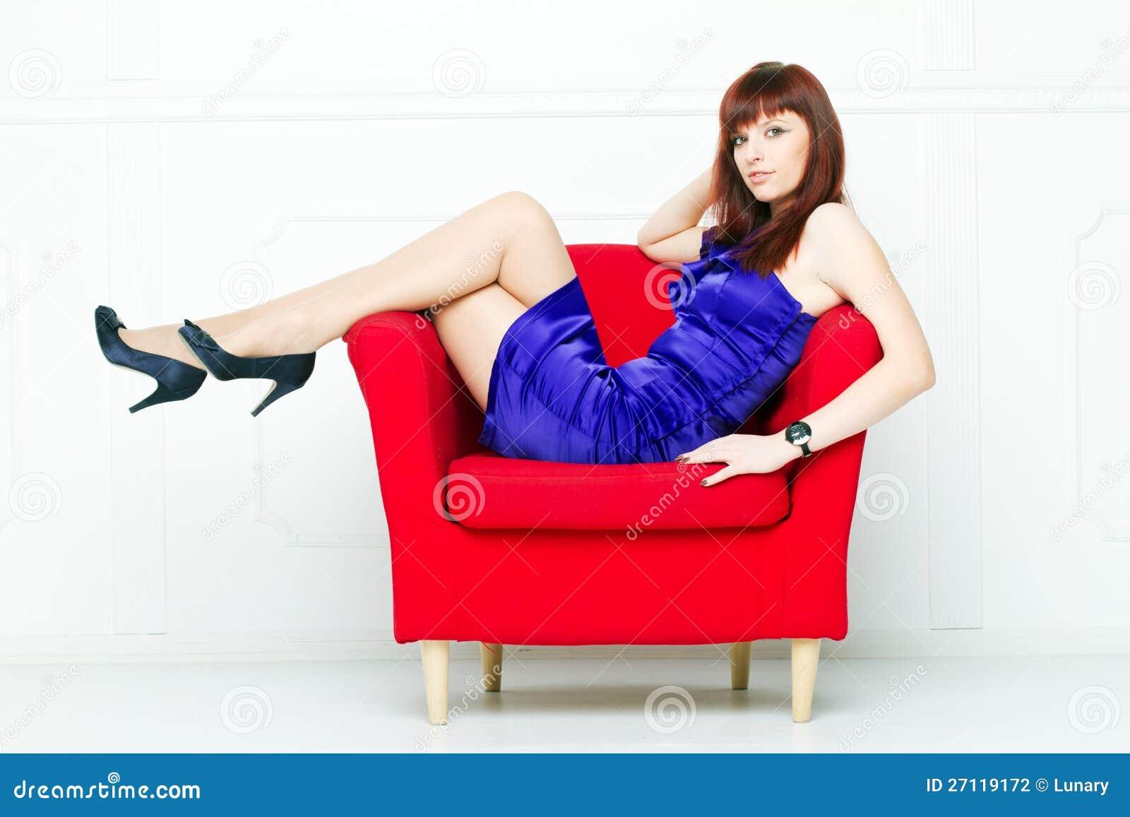 一把红色椅子的新美丽的妇女