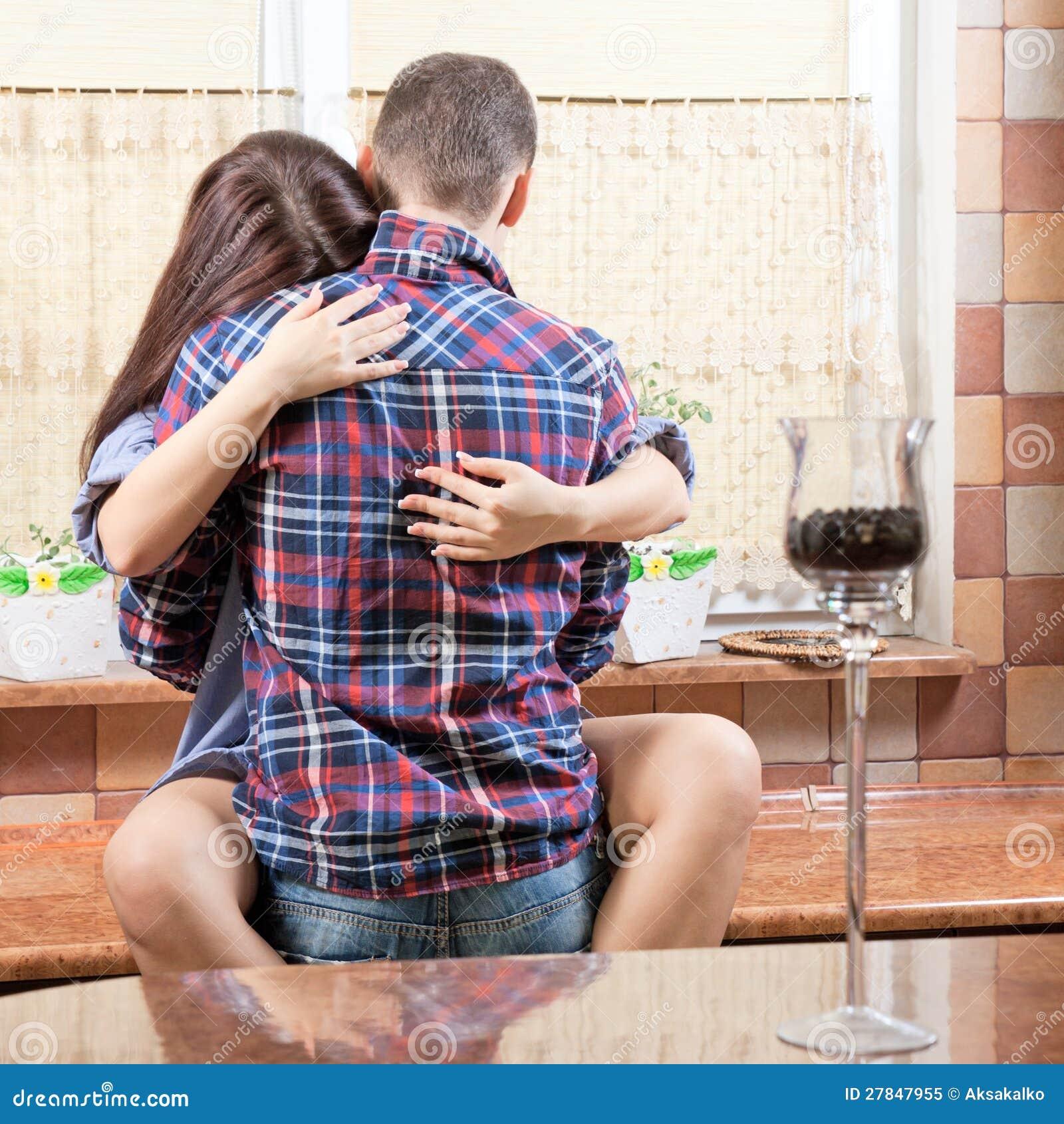 一新夫妇拥抱的纵向每其他厨房.图片