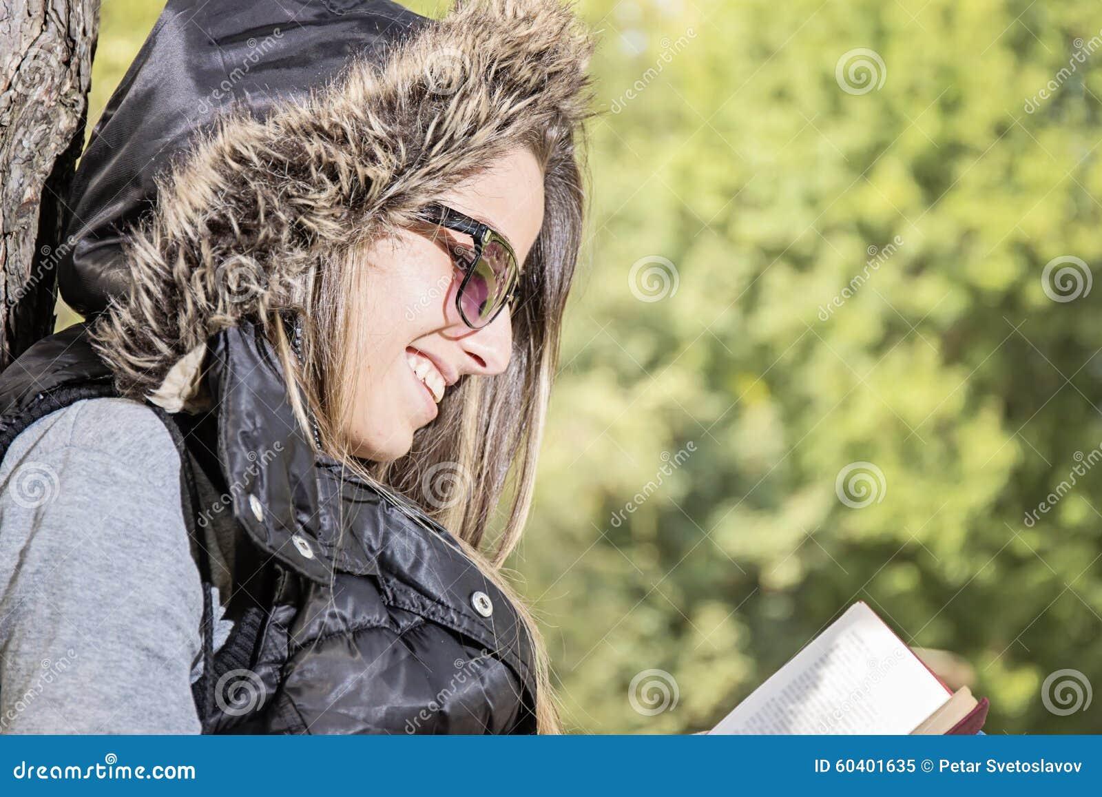 读一本书的美丽的女孩在秋天公园