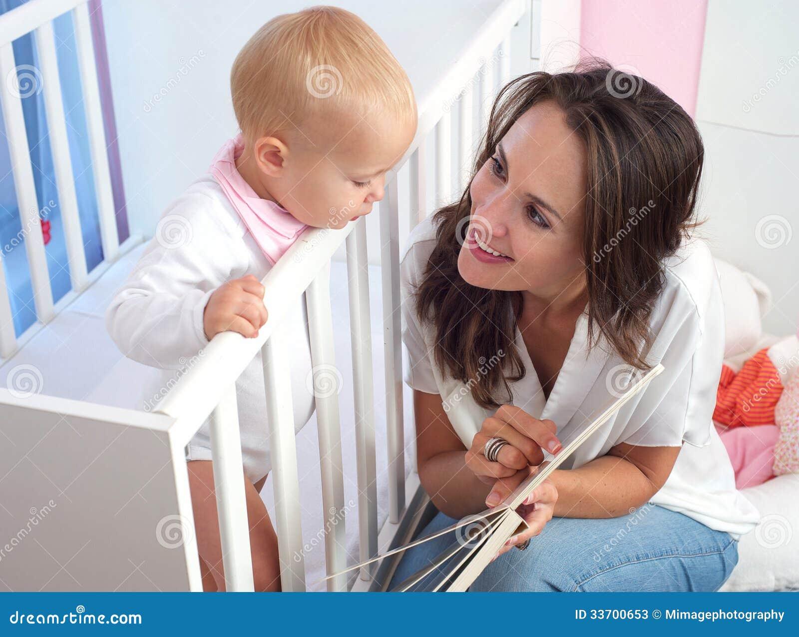 一本美丽的母亲阅读书的画象对逗人喜爱的婴孩的