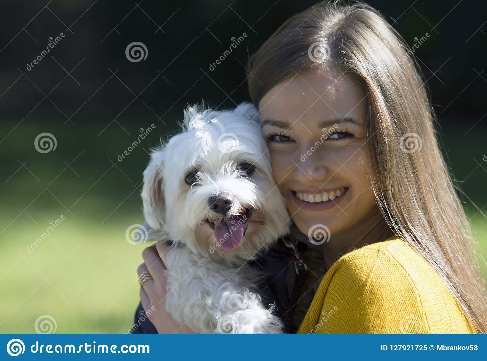 一条小的白色狗的容忍的微笑的女孩 在她的面孔的大微笑