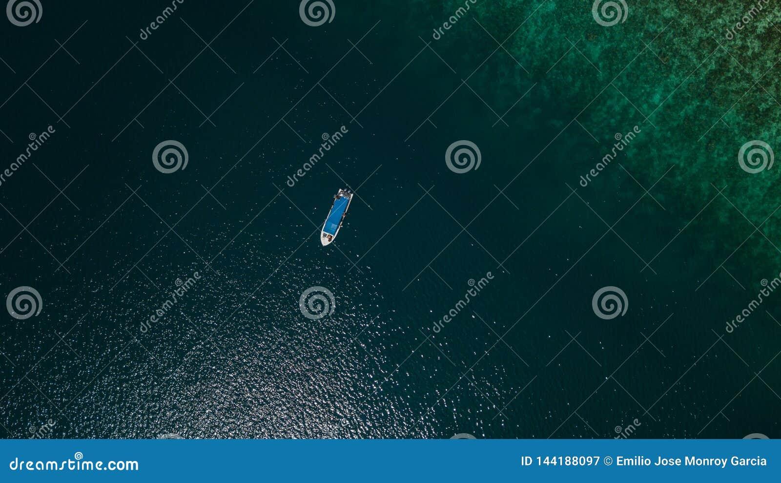 一条小船的鸟瞰图在一块礁石旁边的在海中间