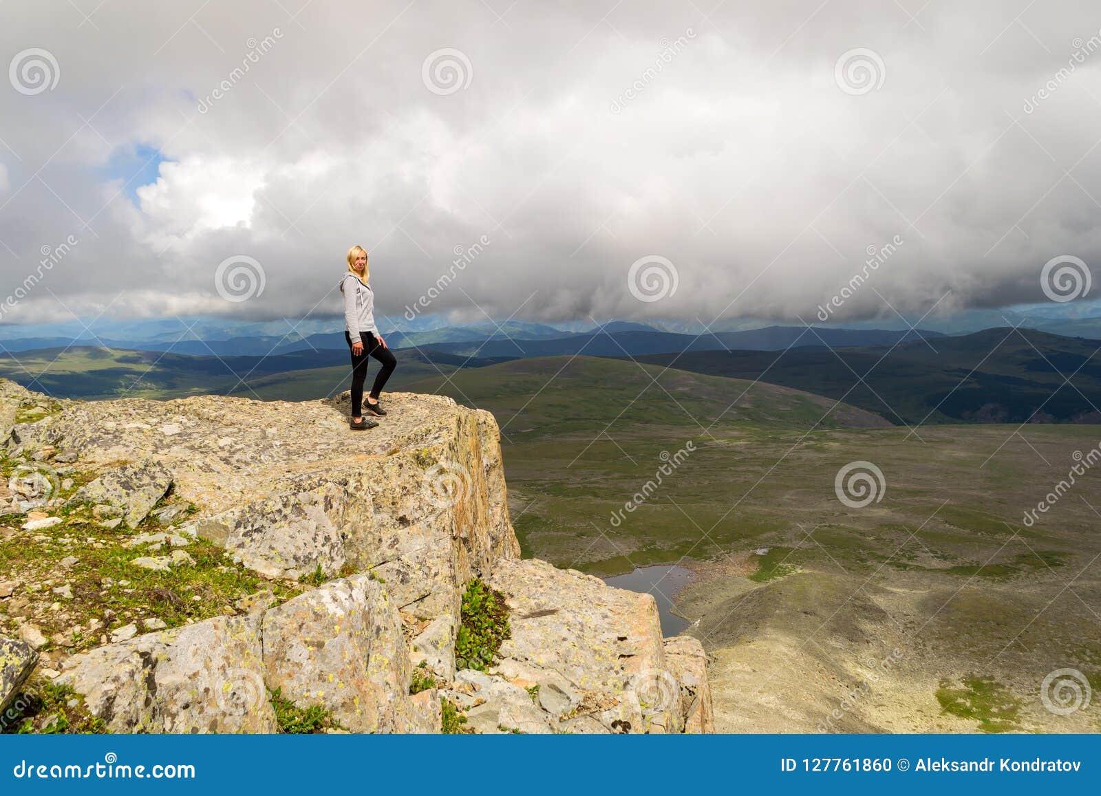 一条灰色hoody,黑长腿的一名年轻白肤金发的妇女在t站立