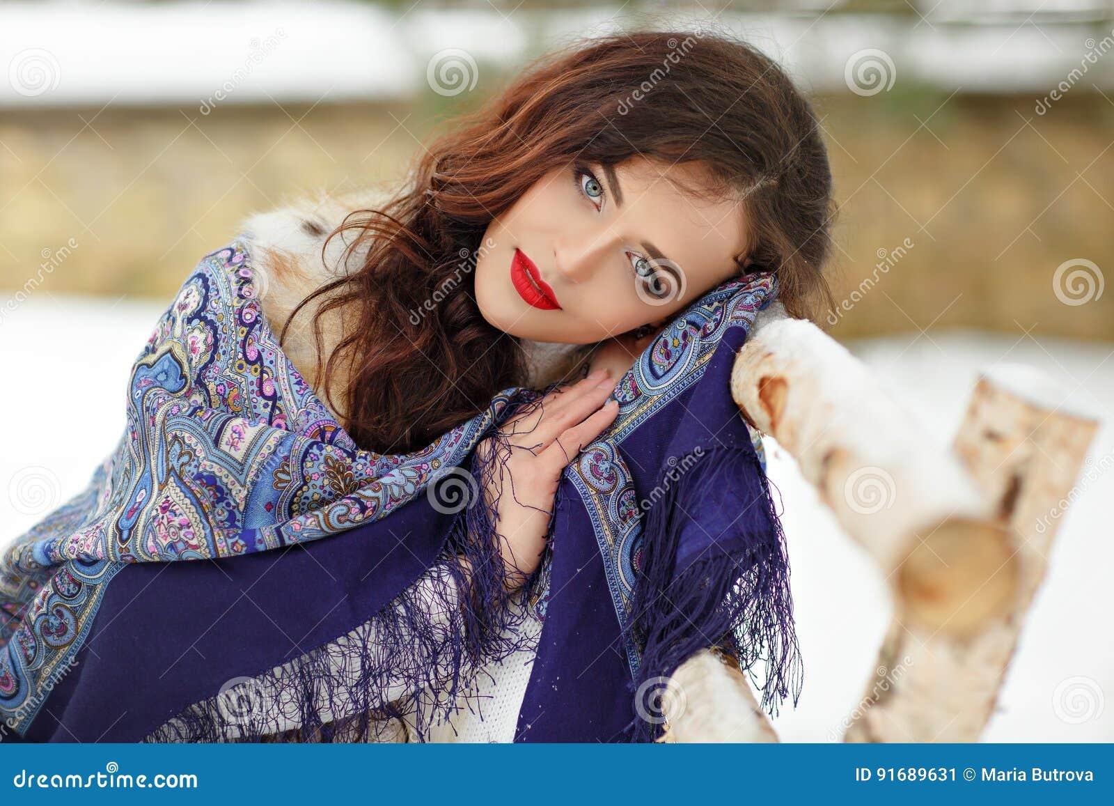 一条蓝色围巾的美丽的性感的深色的女孩在a的冬天