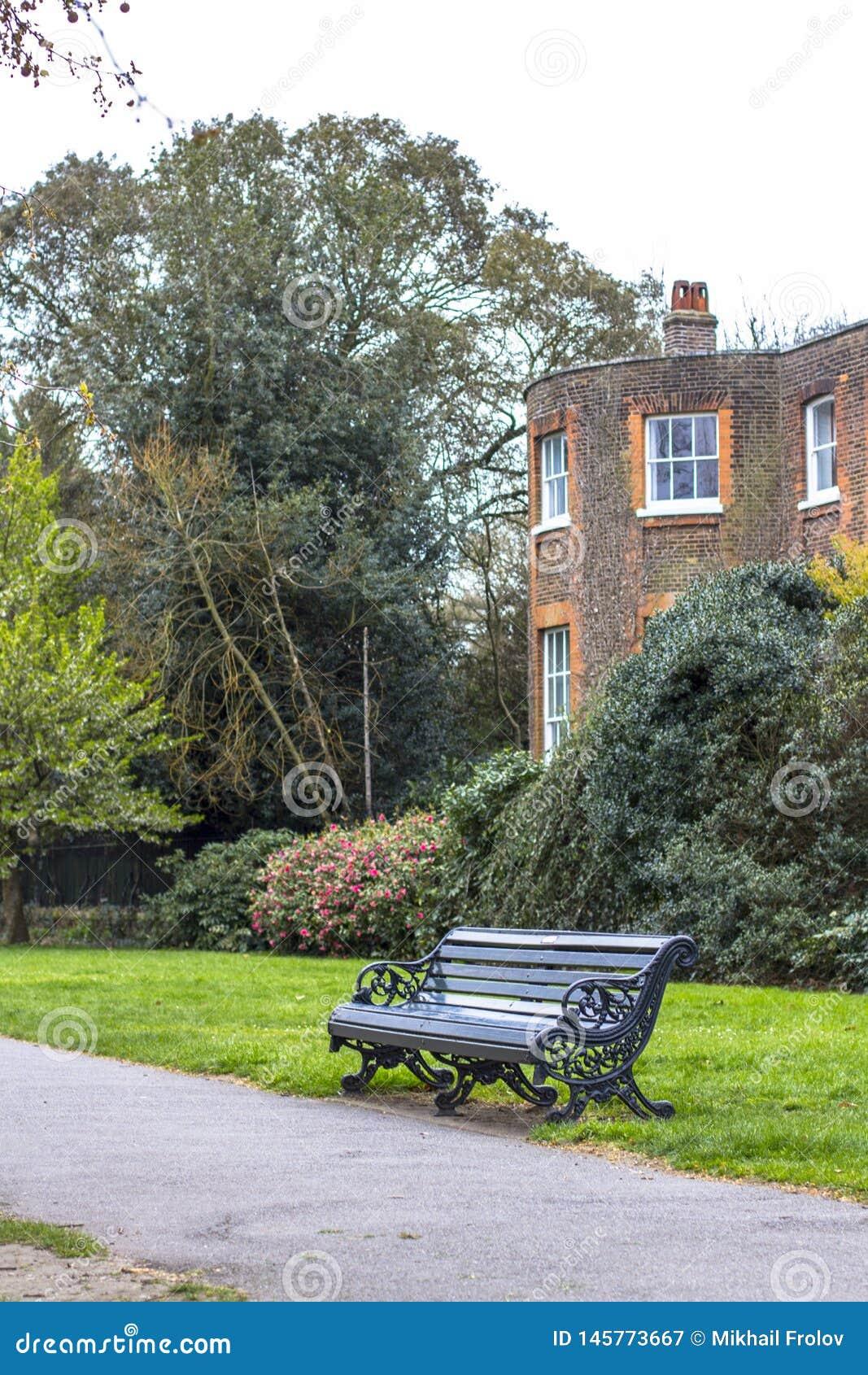 一条长凳在沿道路的公园反对一个经典英国红砖大厦的背景