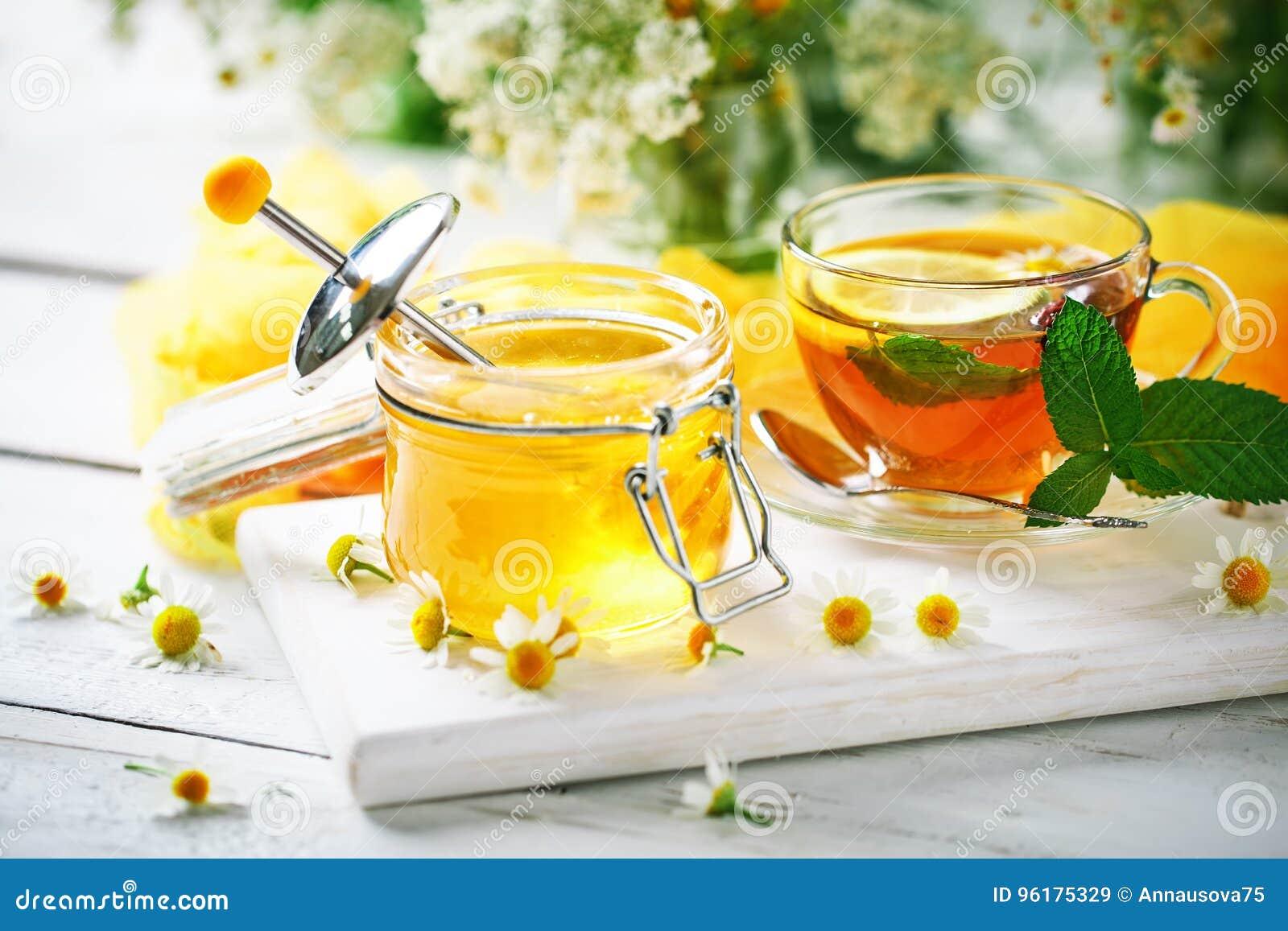一杯健康茶,一个瓶子蜂蜜和花 选择聚焦