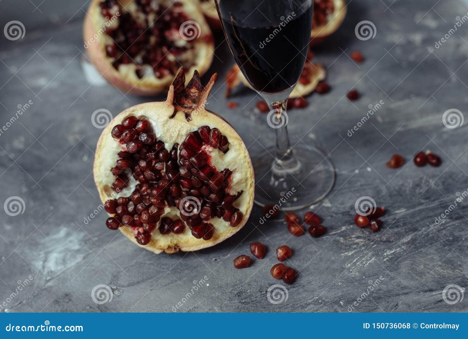一杯在灰色背景的酒在石榴中 接近的石榴和红色石榴种子