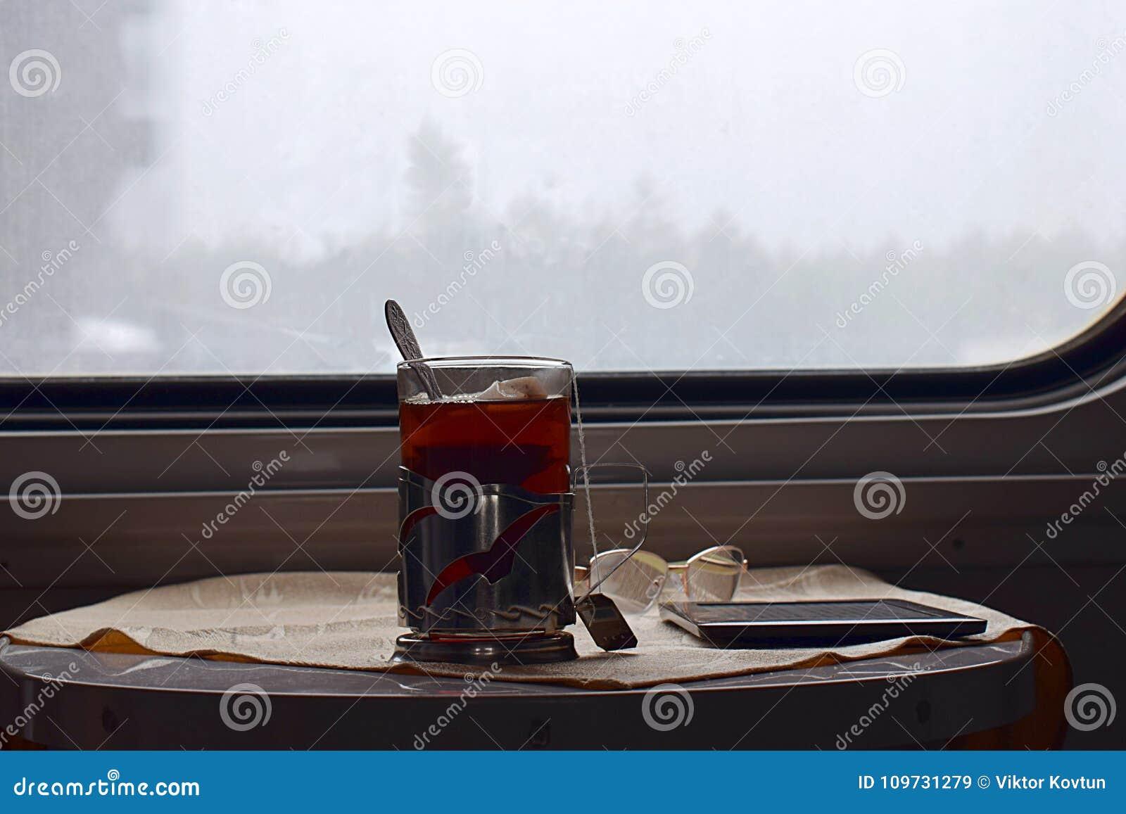一杯茶、一本电子书和玻璃在列车车箱