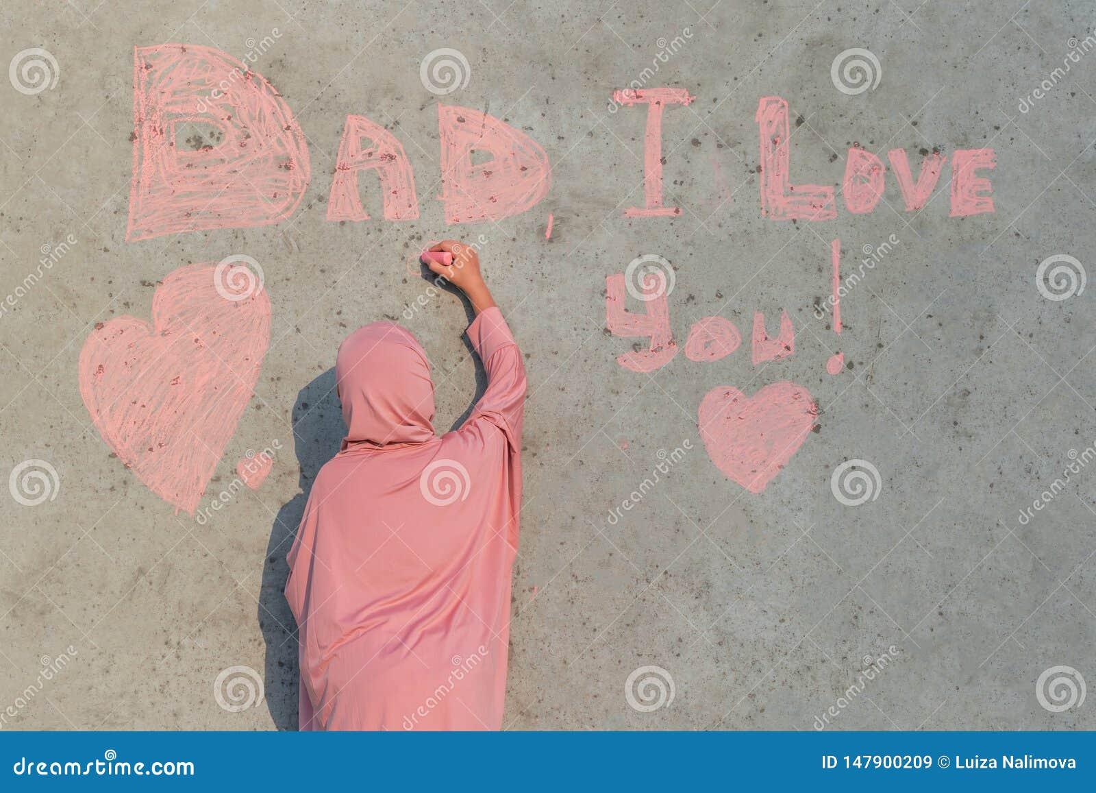 一桃红色hijab的一个女孩与白垩在墙壁爸爸写我爱你 愉快的父亲节的概念
