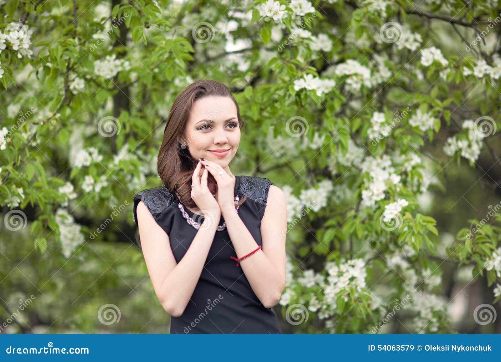 一棵开花的树的背景的女孩