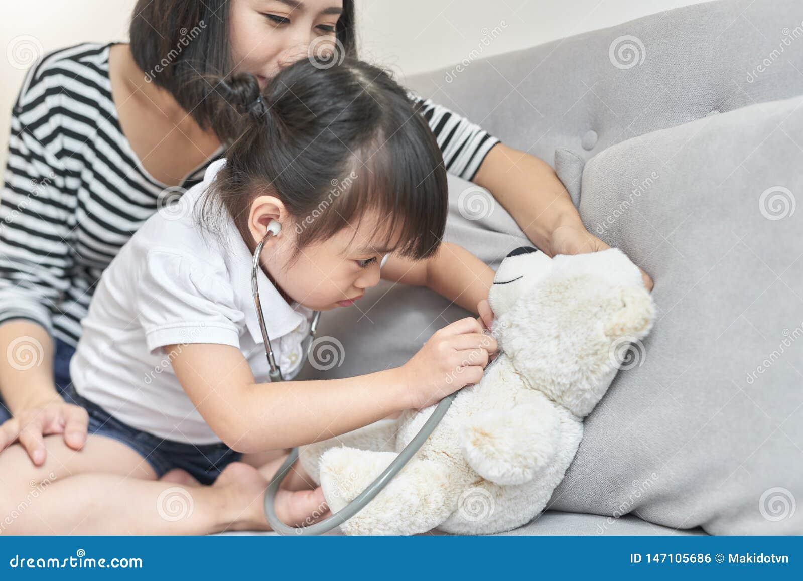 一点与娃娃玩具的亚洲女孩戏剧 小的亚洲女孩举行听诊器在手中和检查娃娃玩具