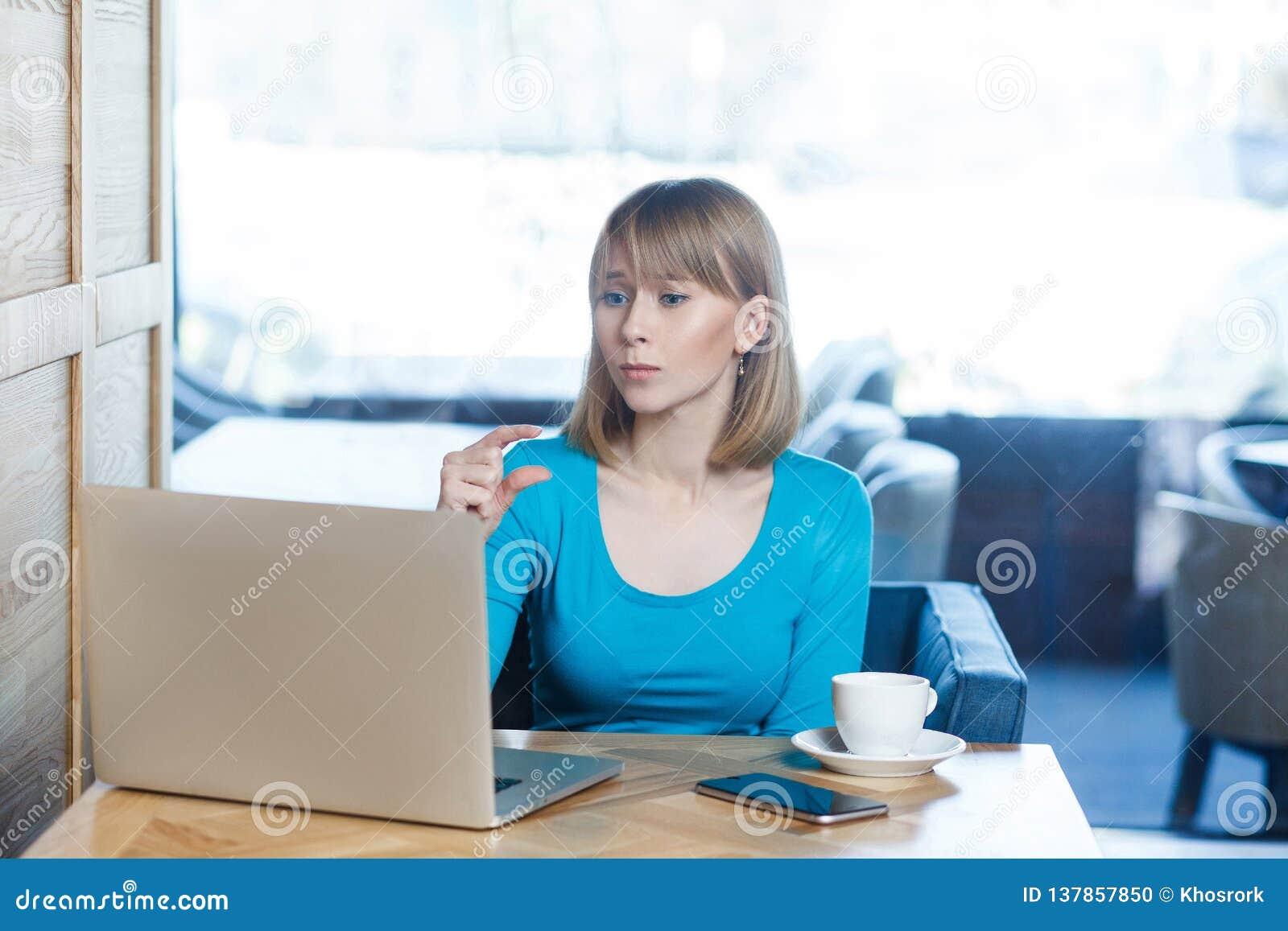 一点位!可爱的少女画象有金发的在蓝色女衬衫在咖啡馆坐,运作并且打视频通话