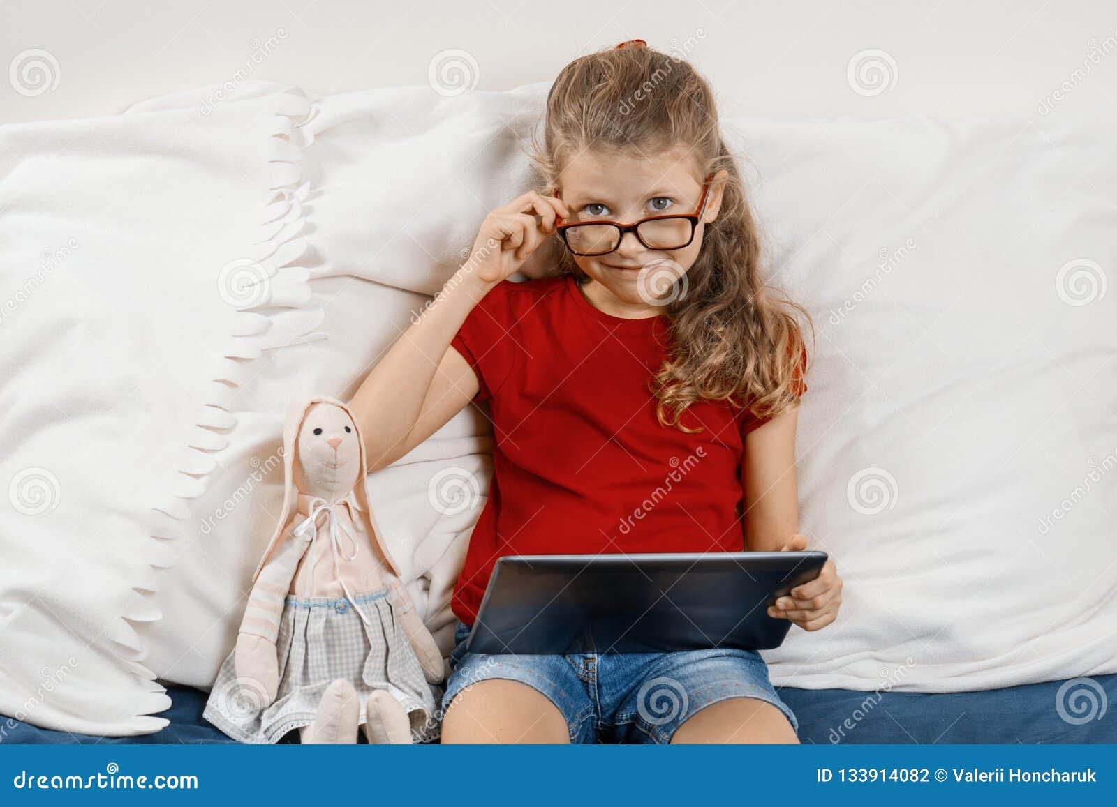 一点在家坐在与玩具的床上的玻璃的俏丽的女孩和数字片剂、休息和教育在家 儿童微笑