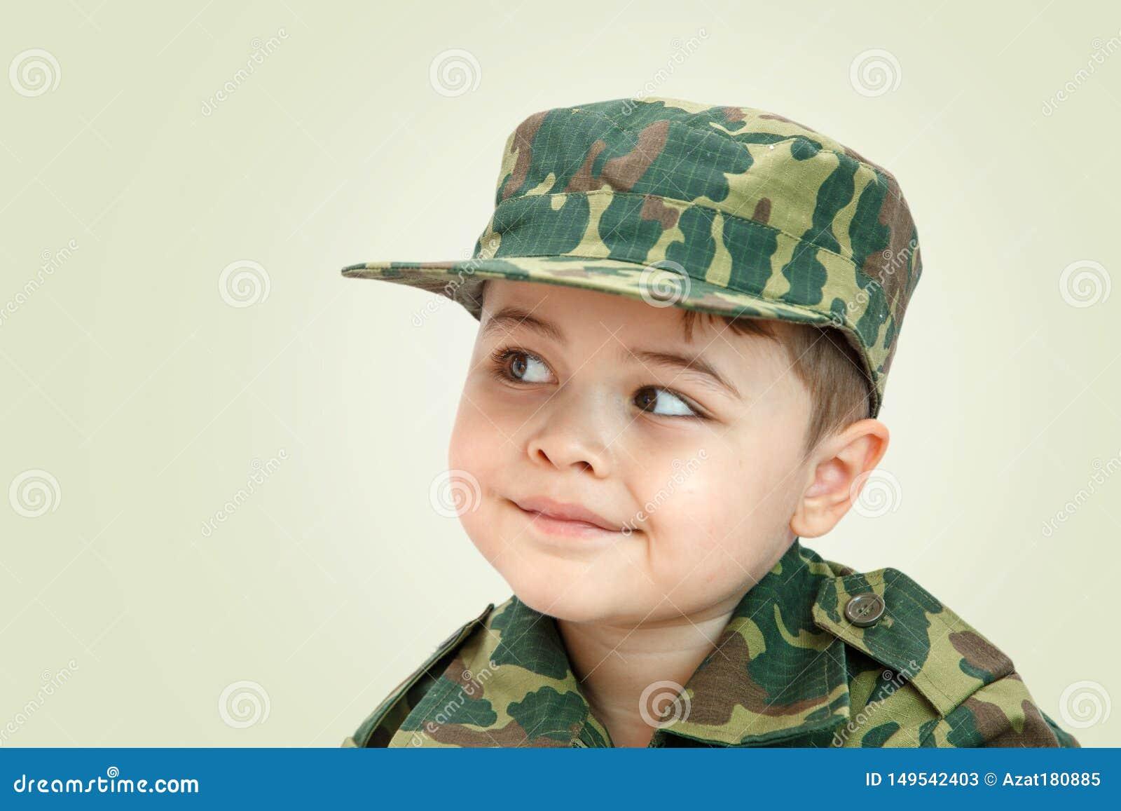 一点在轻的背景隔绝的军用衣裳的白种人男孩