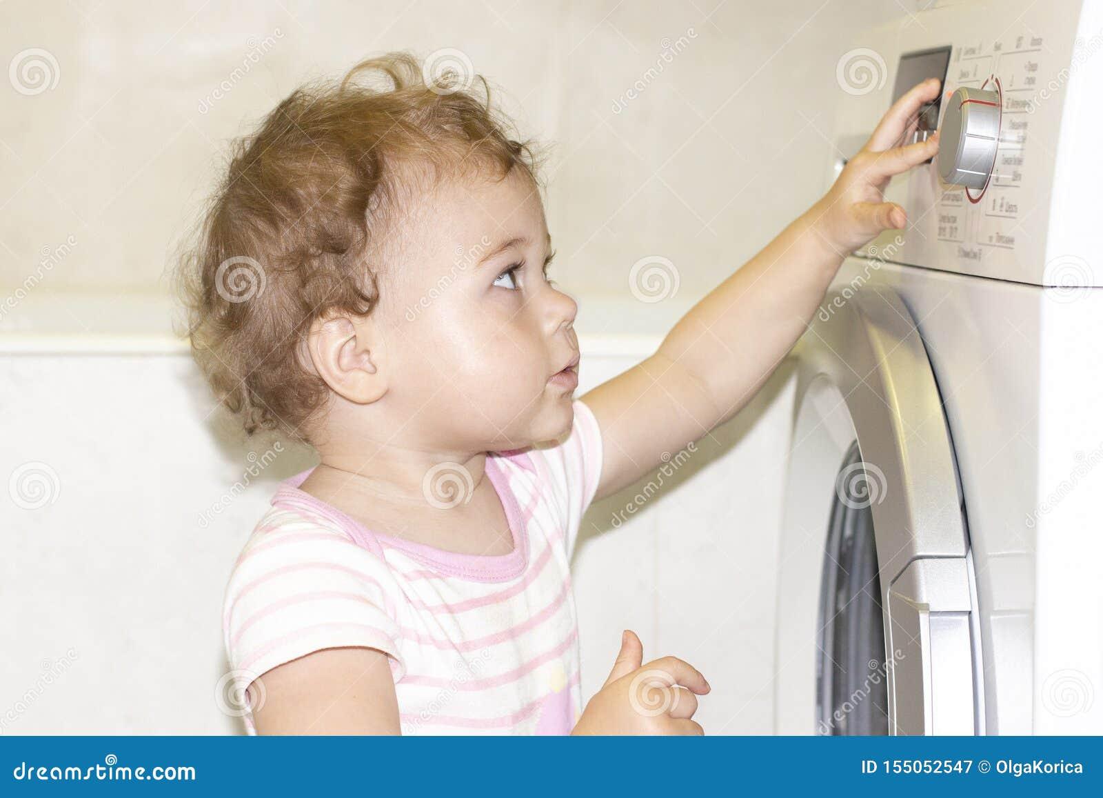 一点女婴按在洗衣机的按钮 欧洲白种人孩子和洗衣机
