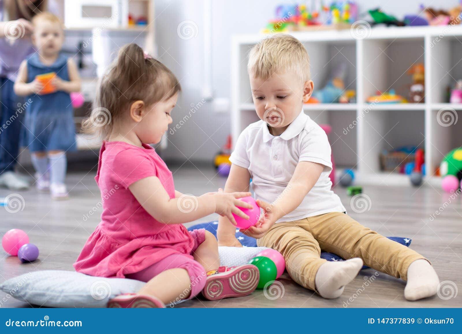 一点小孩男孩和一起使用在托儿所屋子里的女孩 学龄前孩子在日托中心