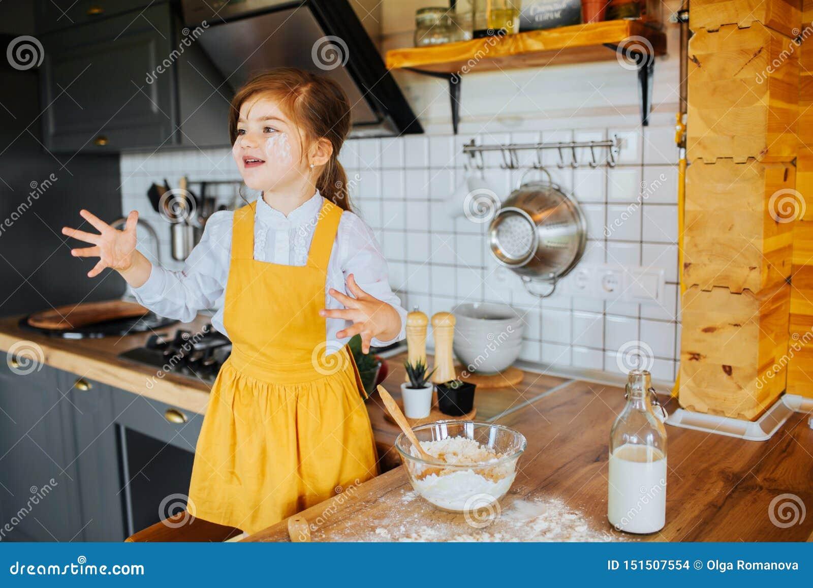 一点戏耍在厨房里的愉快的女孩