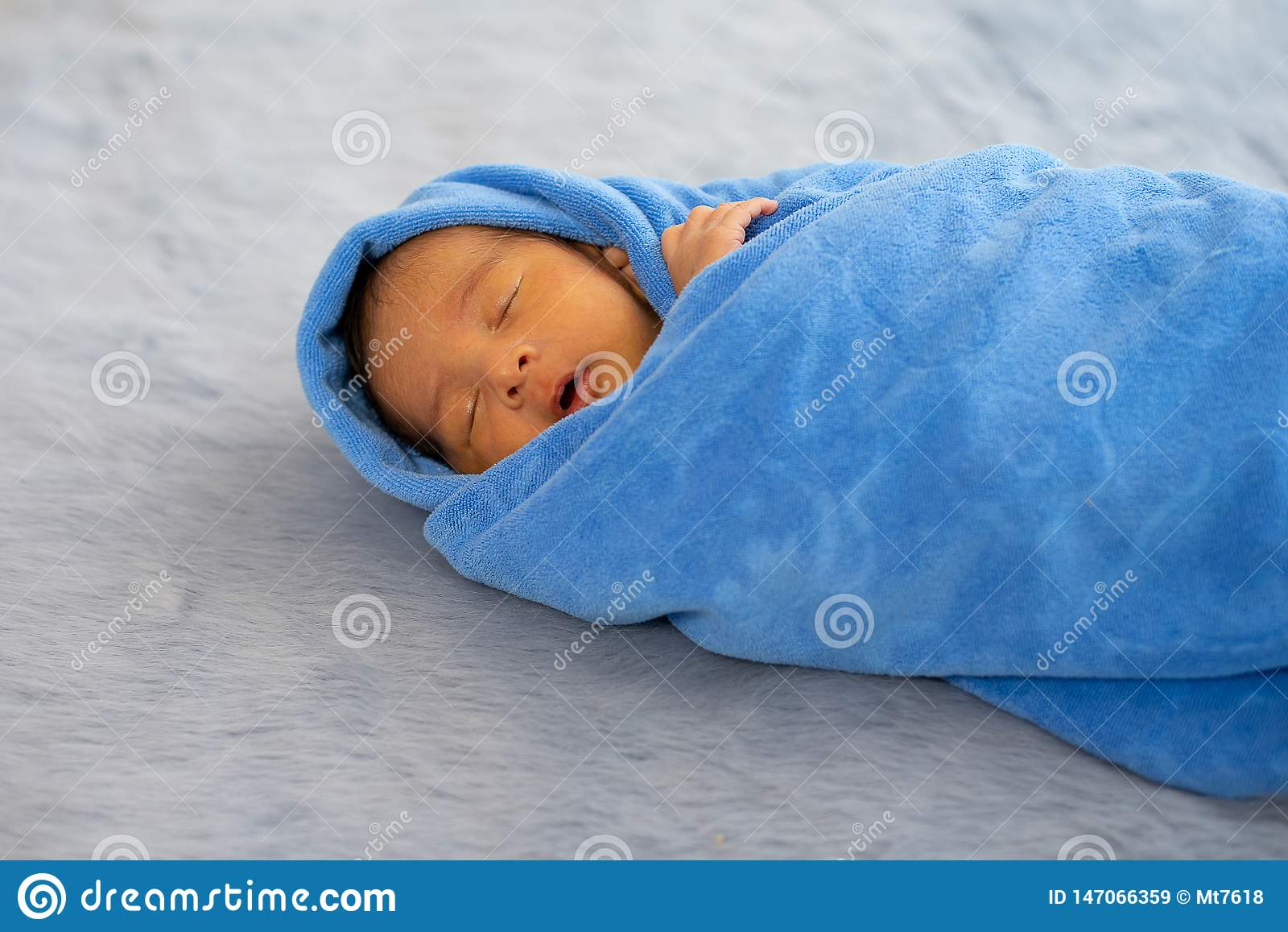 一点新生儿包裹与蓝色毛巾,并且婴孩在灰色地毯睡觉