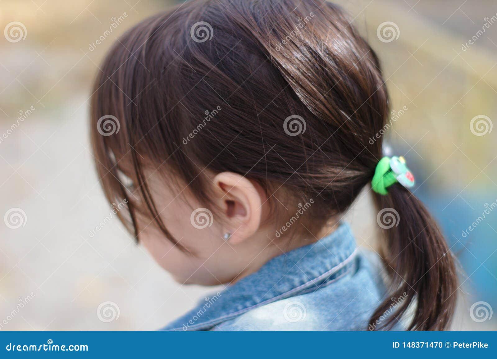 一点逗人喜爱的情感女孩特写镜头画象有猪尾的在牛仔布夹克