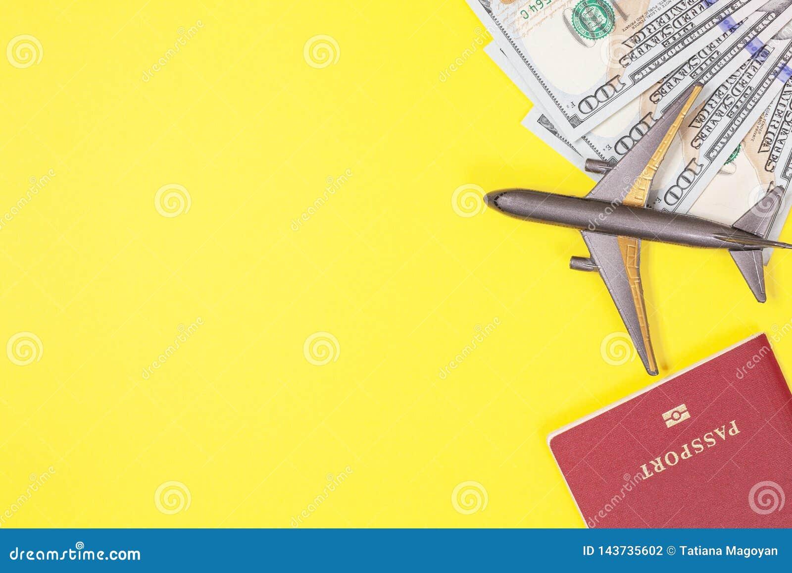 一百元钞票,飞机,耳机,在明亮的黄色纸背景的外国护照 复制空间