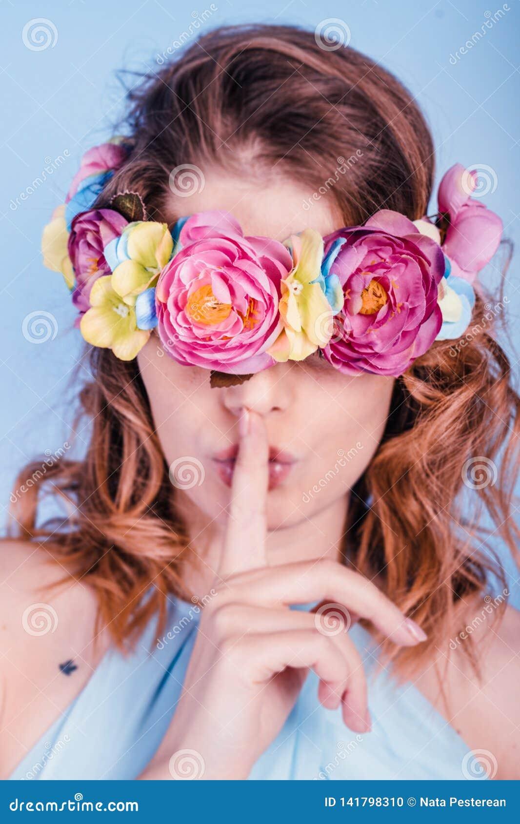 一美丽的白肤金发的年轻女人的接近的画象有花的在她的眼睛和手缠绕在她的嘴唇附近,