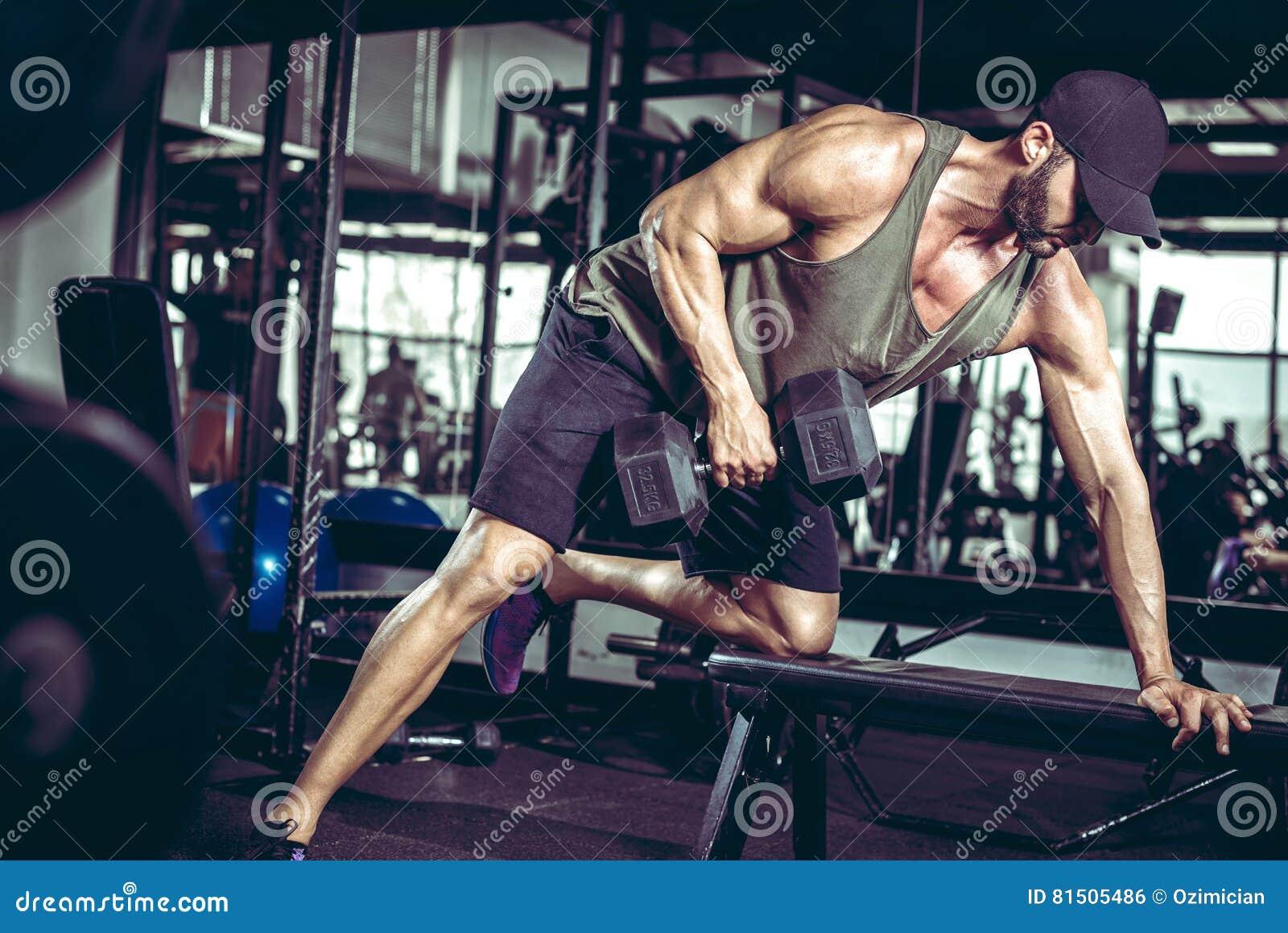 一胳膊在健身房的哑铃行