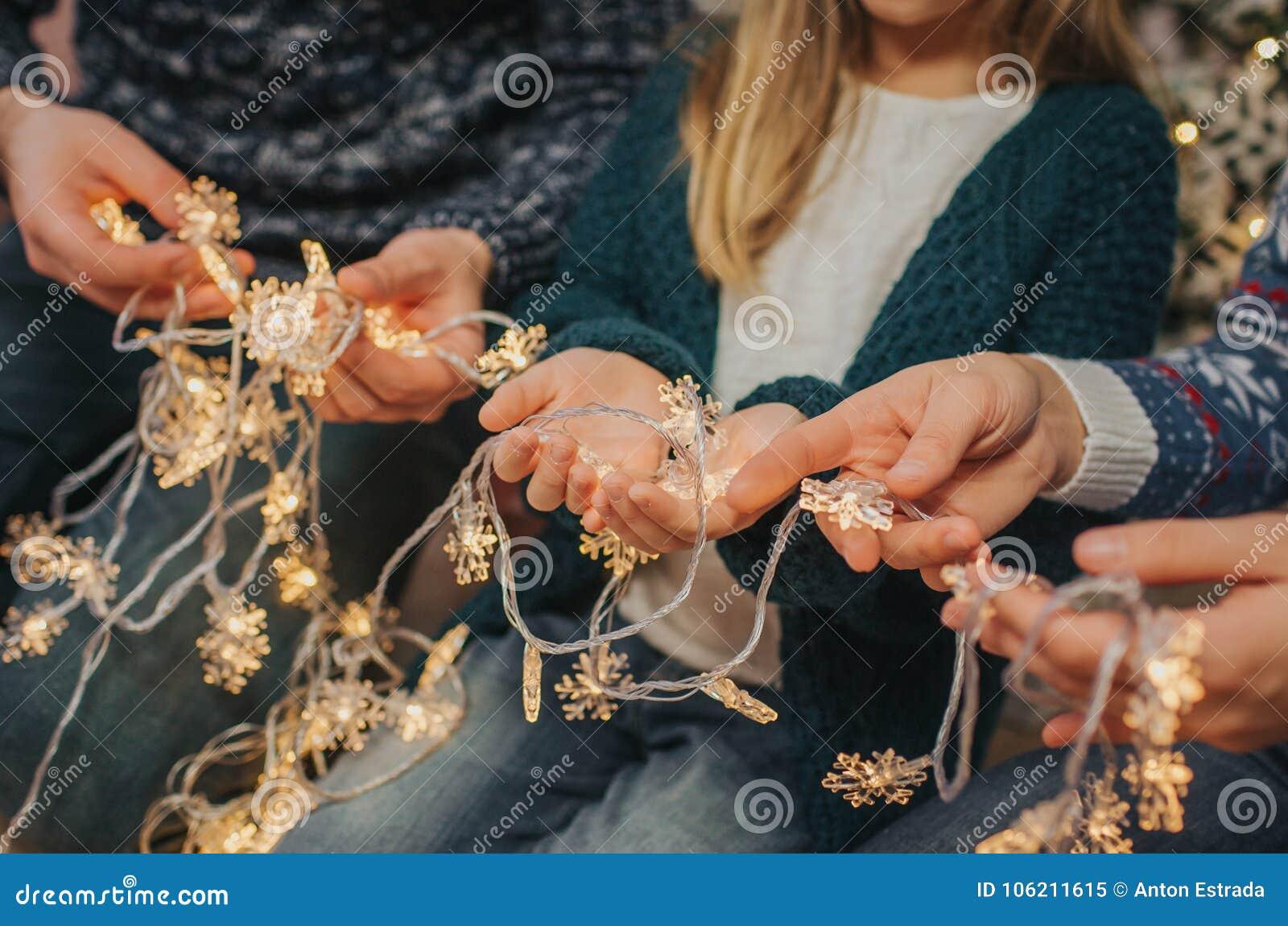 一起享受他们的假日时间的美丽的年轻家庭,装饰圣诞树,安排圣诞灯