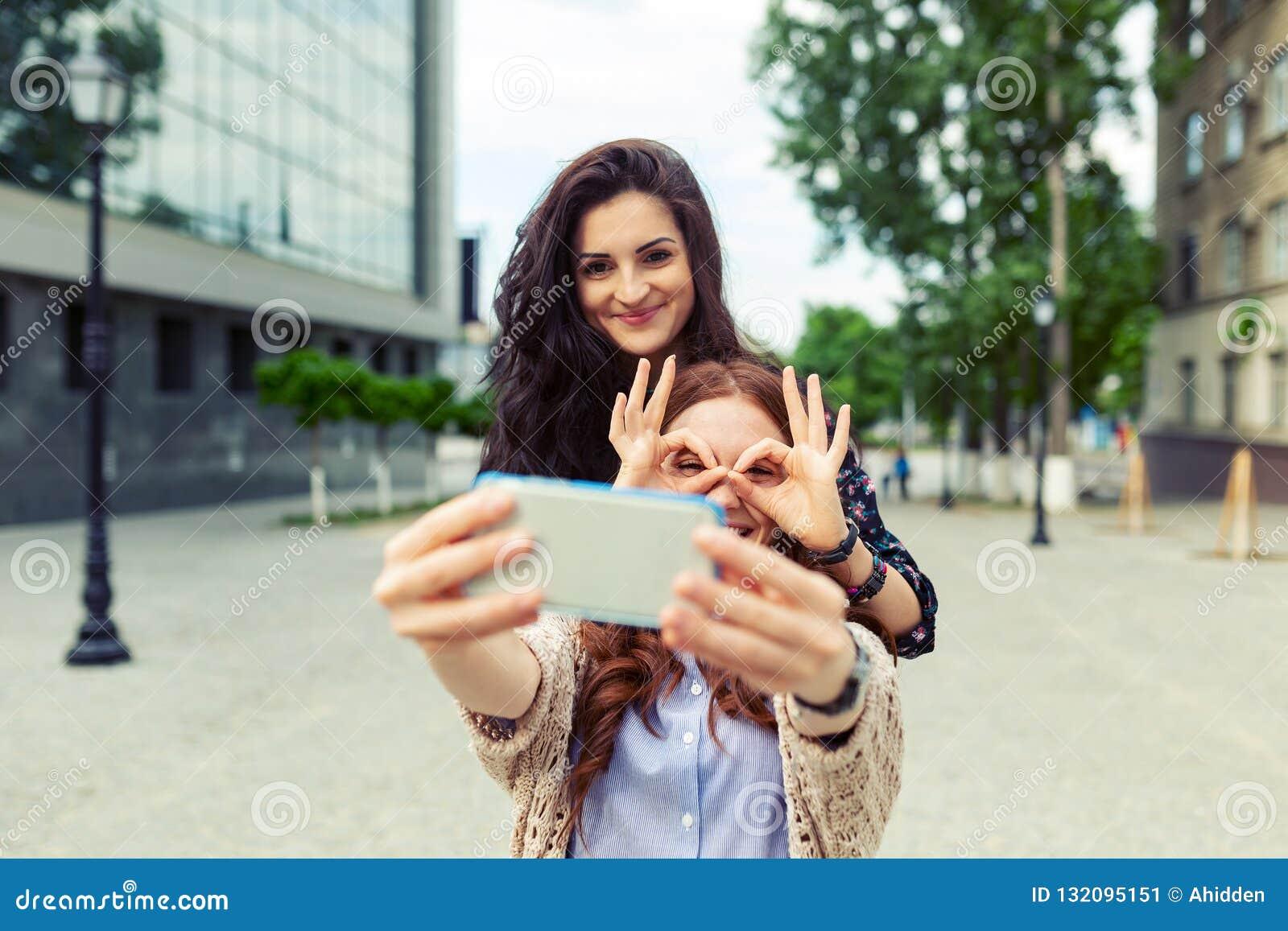 一起做滑稽的selfie的两个女孩在街道,获得乐趣