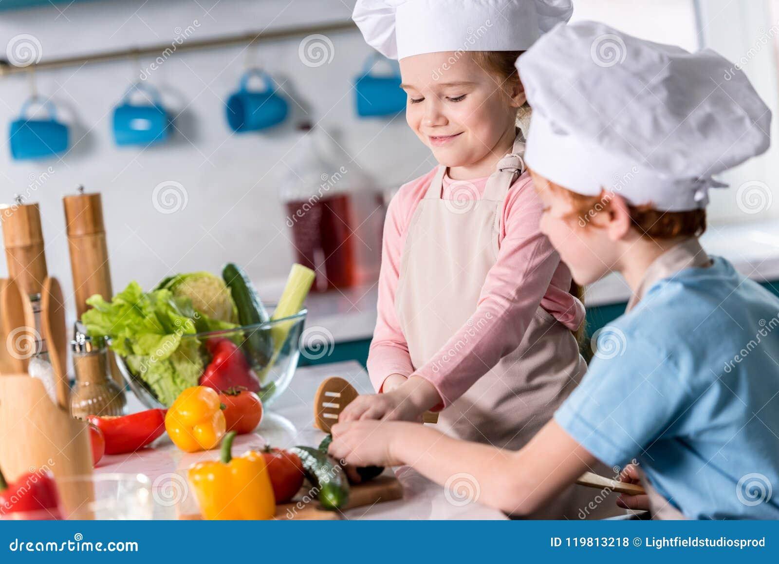 一起准备菜沙拉的厨师帽子的逗人喜爱的小孩